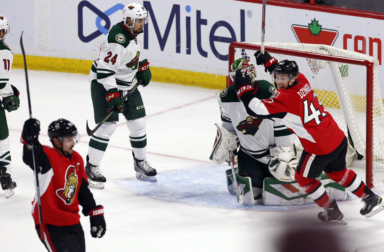 Minnesota Wild goaltender Devan Dubnyk (40) and teammate Matt Dumba (24) react as Ottawa Senators' Erik Karlsson, front left, celebrates his overtime goal with teammate Ryan Dzingel (43) in an NHL hockey game Tuesday, March 15, 2016, in Ottawa, Ontario. (