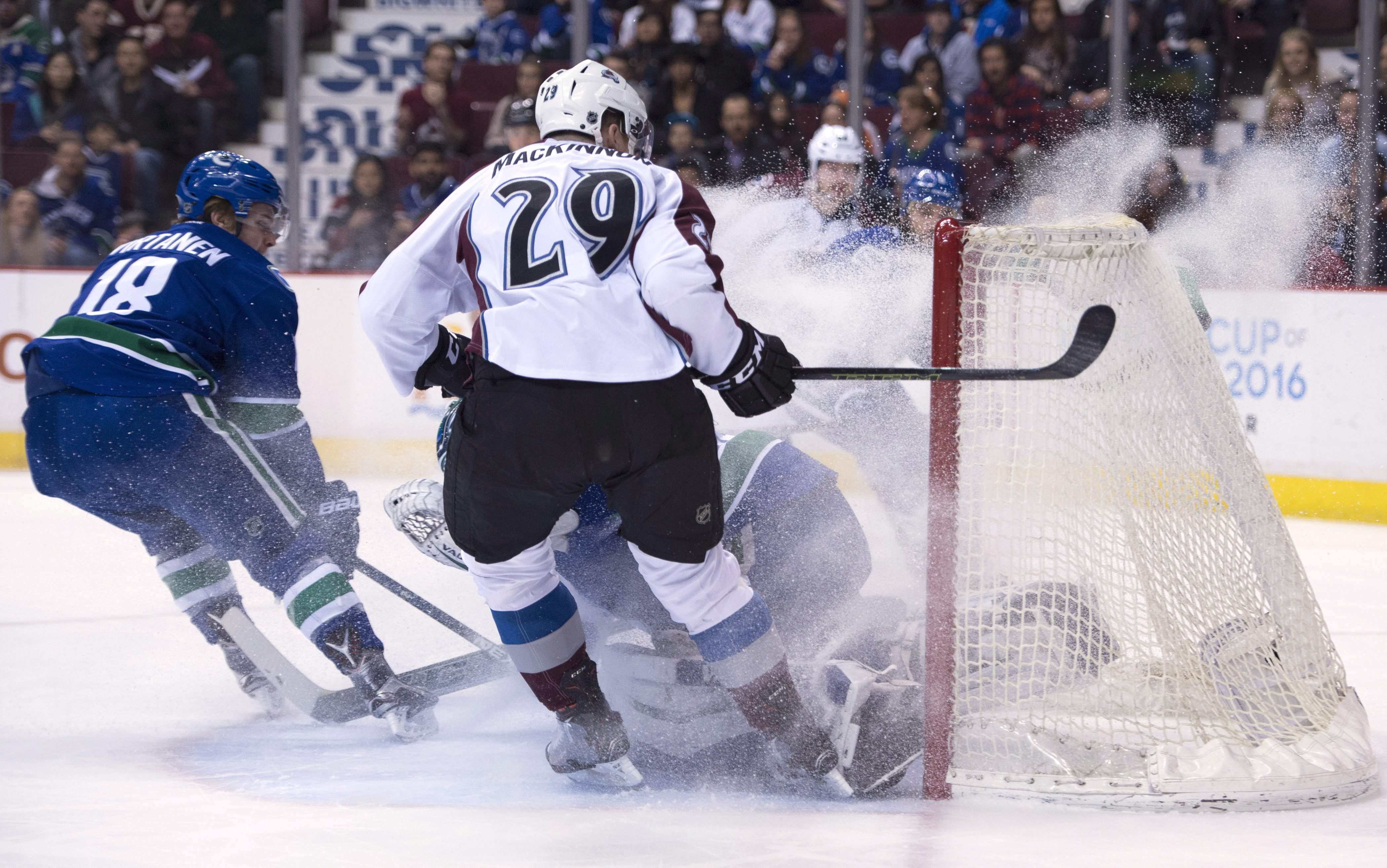 Vancouver Canucks goalie Ryan Miller (30) gets sprayed with ice shavings from Colorado Avalanche center Nathan MacKinnon (29) as Canucks right wing Jake Virtanen (18) watches during the first period of an NHL hockey game Wednesday, March 16, 2016, in Vanc