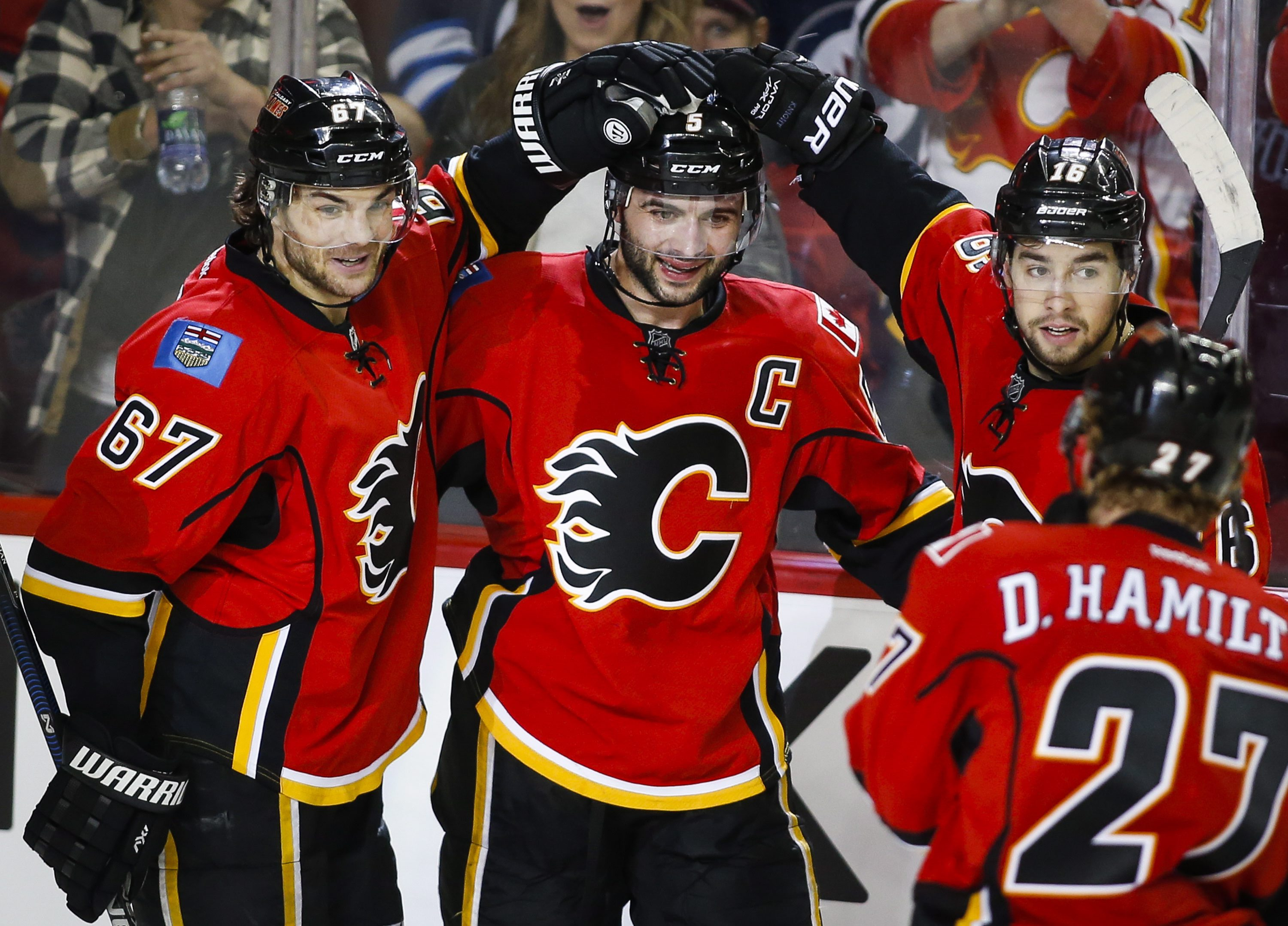 Calgary Flames' Mark Giordano, center, celebrates his goal with teammates Michael Frolik, left, from the Czech Republic, and Josh Jooris during the third period of an NHL hockey game against the Winnipeg Jets on Wednesday, March 16, 2016, in Calgary, Albe
