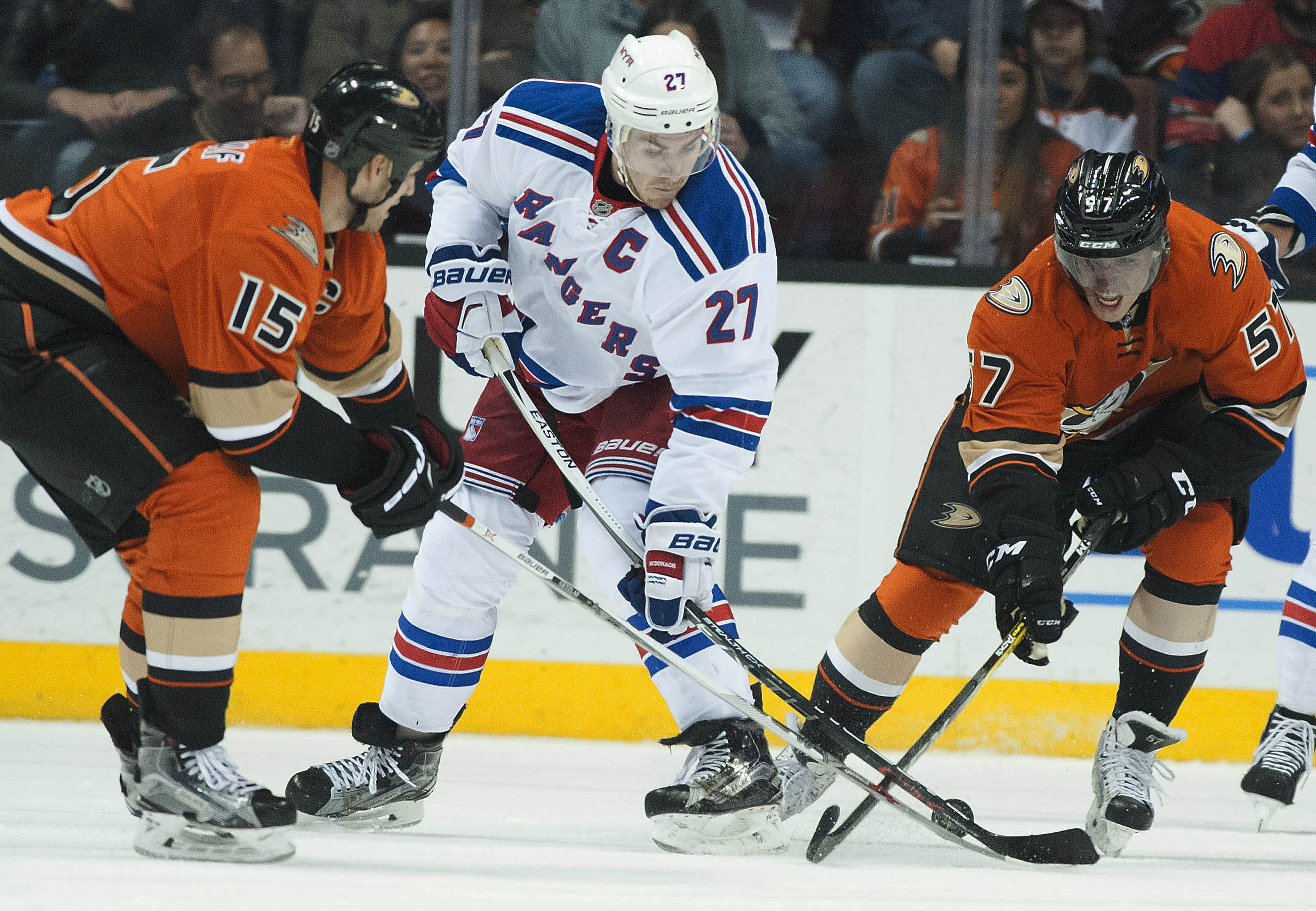 The Ducks' Ryan Getzlaf, left, and David Perron battle the Rangers' Ryan McDonagh for the puck during the second period of their NHL hockey game in Anaheim, Calif., on Wednesday, March 16, 2016. (Kevin Sullivan/The Orange County Register via AP) MANDATORY