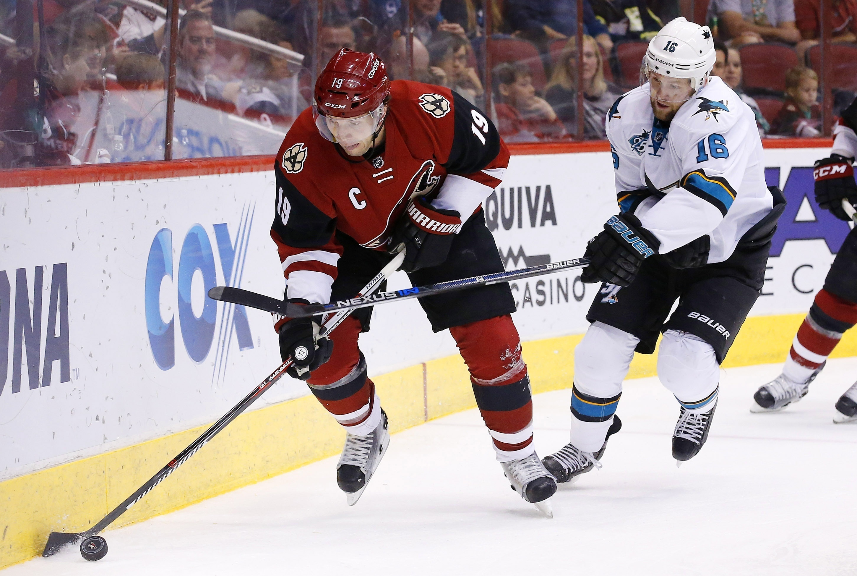Arizona Coyotes' Shane Doan (19) tries to skate with the puck as San Jose Sharks' Nick Spaling (16) arrives to hit Doan with his stick during the first period of an NHL hockey game Thursday, March 17, 2016, in Glendale, Ariz. (AP Photo/Ross D. Franklin)