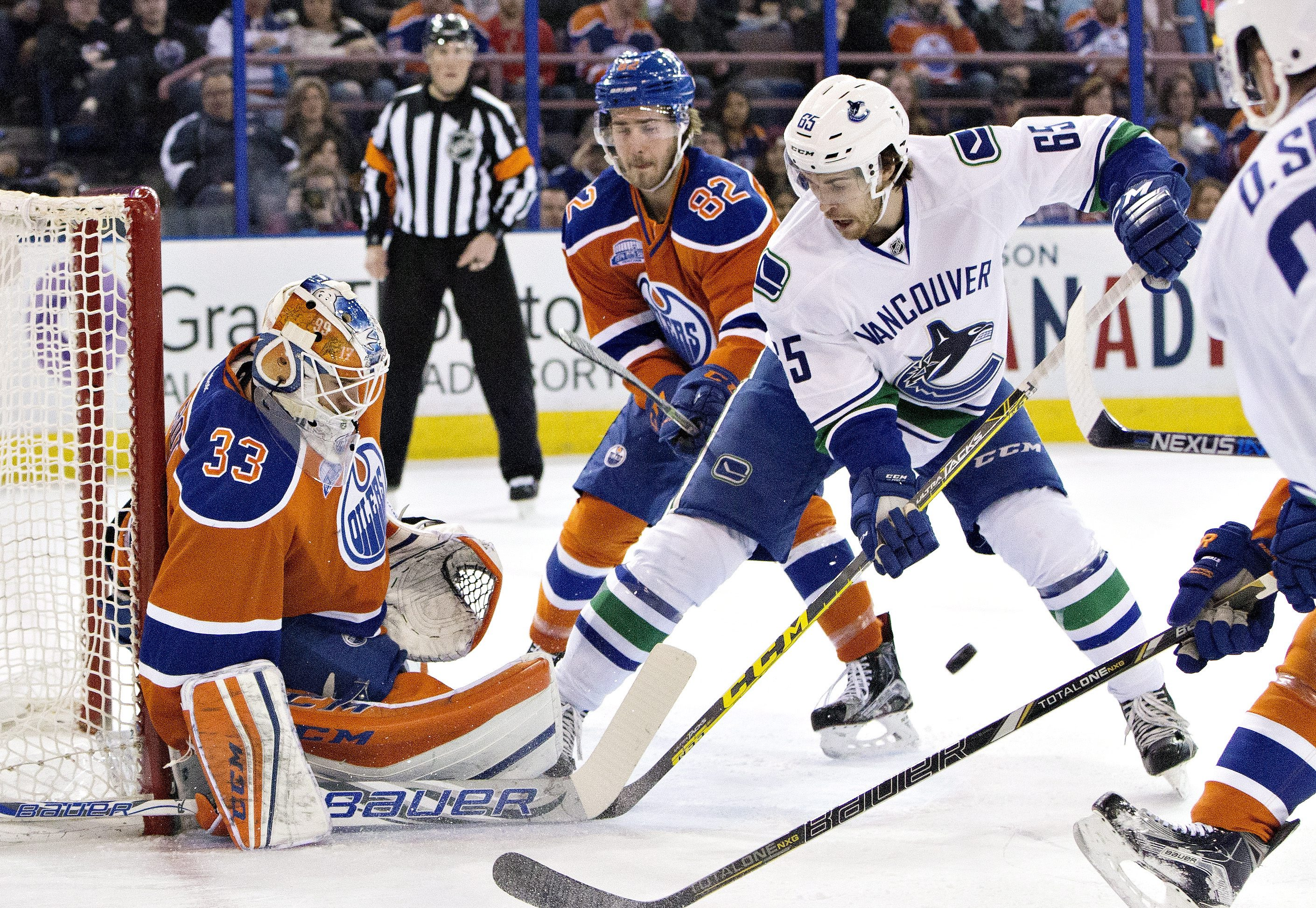 Vancouver Canucks' Alexandre Grenier (65) is stopped by Edmonton Oilers' goalie Cam Talbot (33) as Jordan Oesterle (82) defends during the first period of an NHL hockey game, Friday, March 18, 2016 in Edmonton, Alberta.  (Jason Franson/The Canadian Press