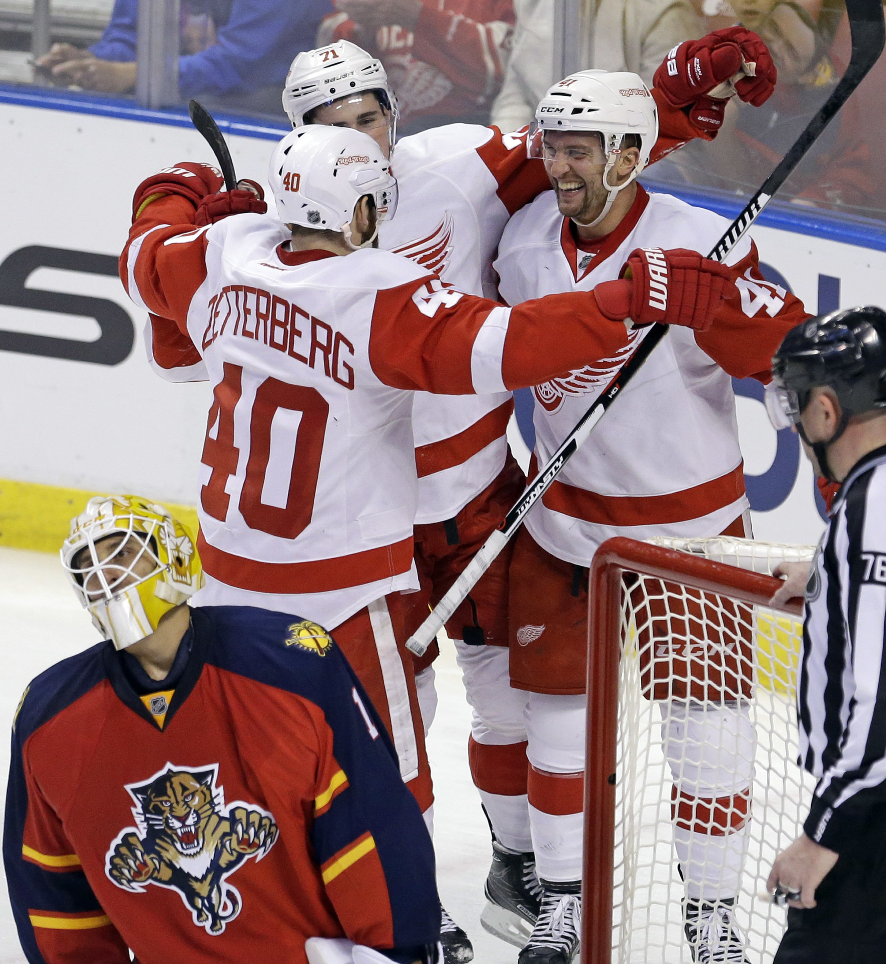 Detroit Red Wings center Luke Glendening (41) is congratulated by teammates after scoring a goal against Florida Panthers goalie Roberto Luongo (1) during the third period of an NHL hockey game in Sunrise, Fla., Saturday, March 19, 2016. (AP Photo/Alan Di