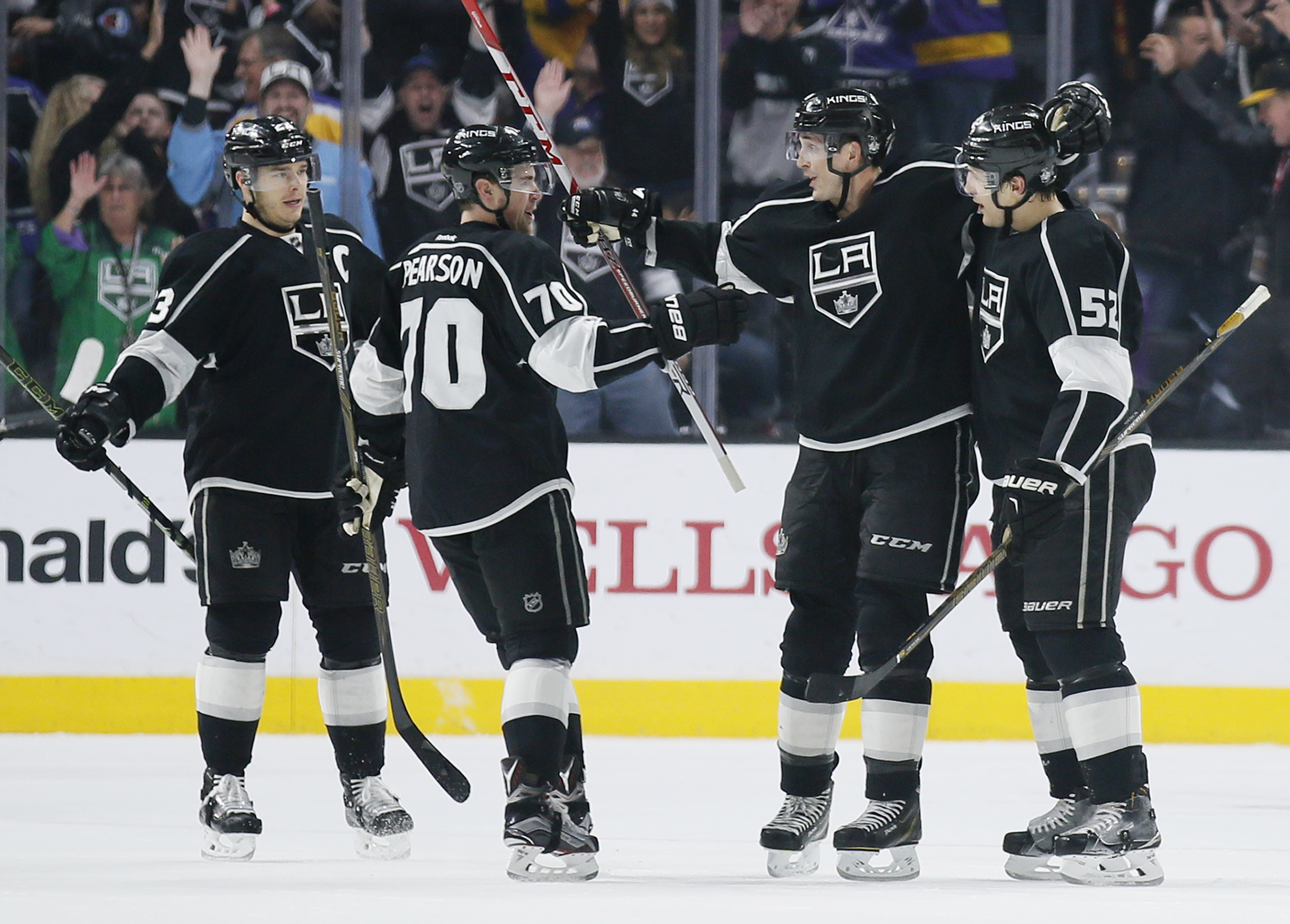 Los Angeles Kings left wing Tanner Pearson, second left, celebrates his goal with teammates, from left to right, Dustin Brown, Vincent Lecavalier, and Luke Schenn against the Boston Bruins during the first period of an NHL hockey game, Saturday, March 19,