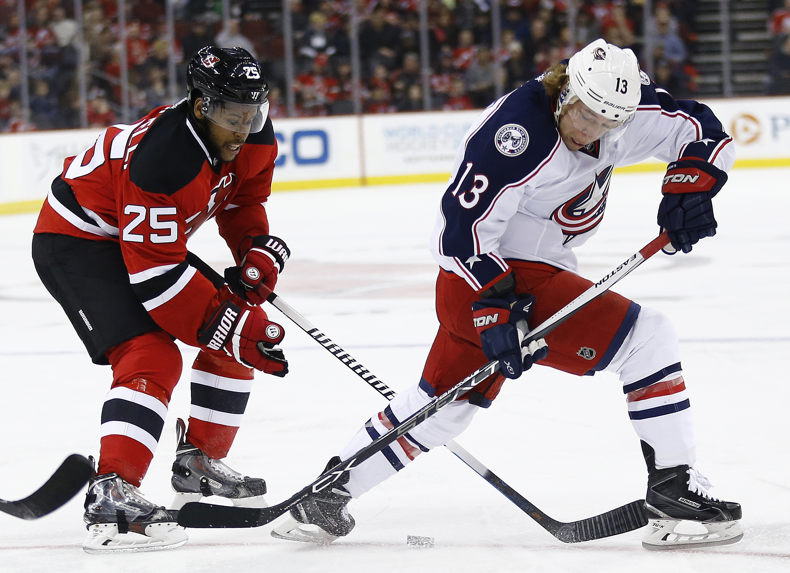 Columbus Blue Jackets right wing Cam Atkinson (13) and New Jersey Devils right wing Devante Smith-Pelly (25) compete for the puck during the first period of an NHL hockey game, Sunday, March 20, 2016, in Newark, N.J. (AP Photo/Julio Cortez)