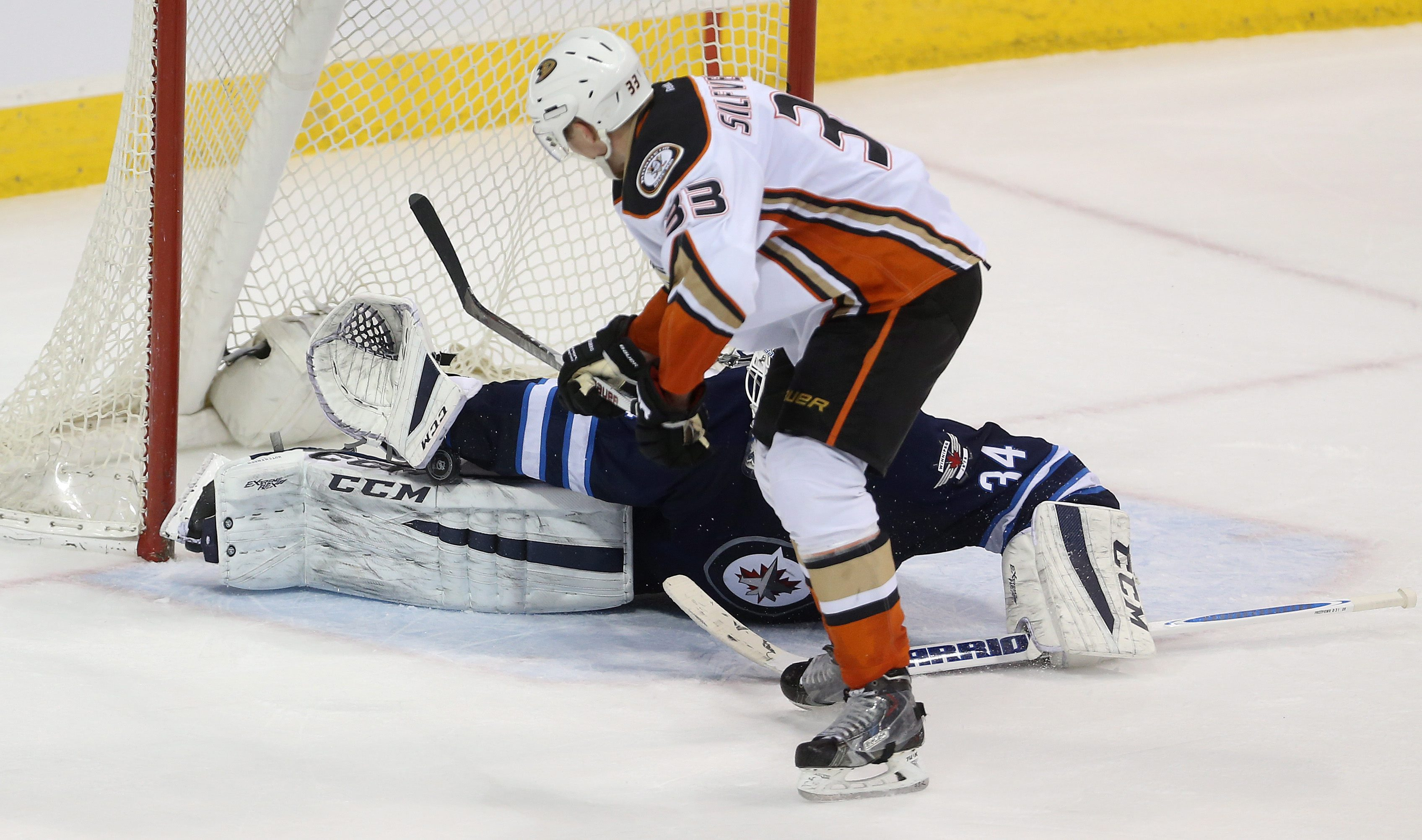 Winnipeg Jets' goaltender Michael Hutchinson (34) stretches across the net to make the first save on Anaheim Ducks Jakob Silfverberg (33), but he would score on his own rebound during overtime NHL hockey action in Winnipeg, Canada, Sunday, March 20, 2016.