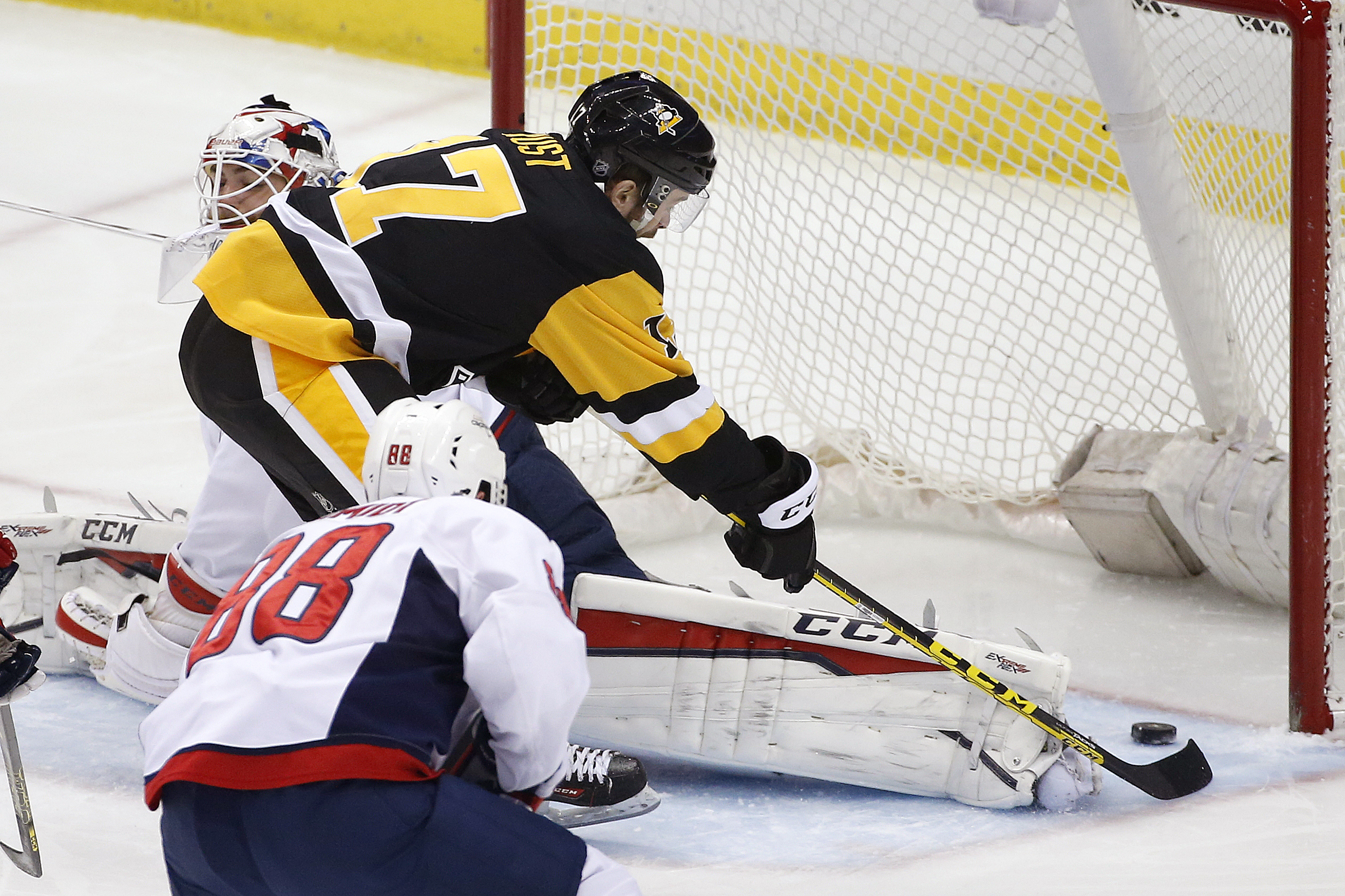 Pittsburgh Penguins' Bryan Rust (17) puts the puck behind Washington Capitals goalie Braden Holtby (70) for a goal during the first period of an NHL hockey game in Pittsburgh, Sunday, March 20, 2016. (AP Photo/Gene J. Puskar)