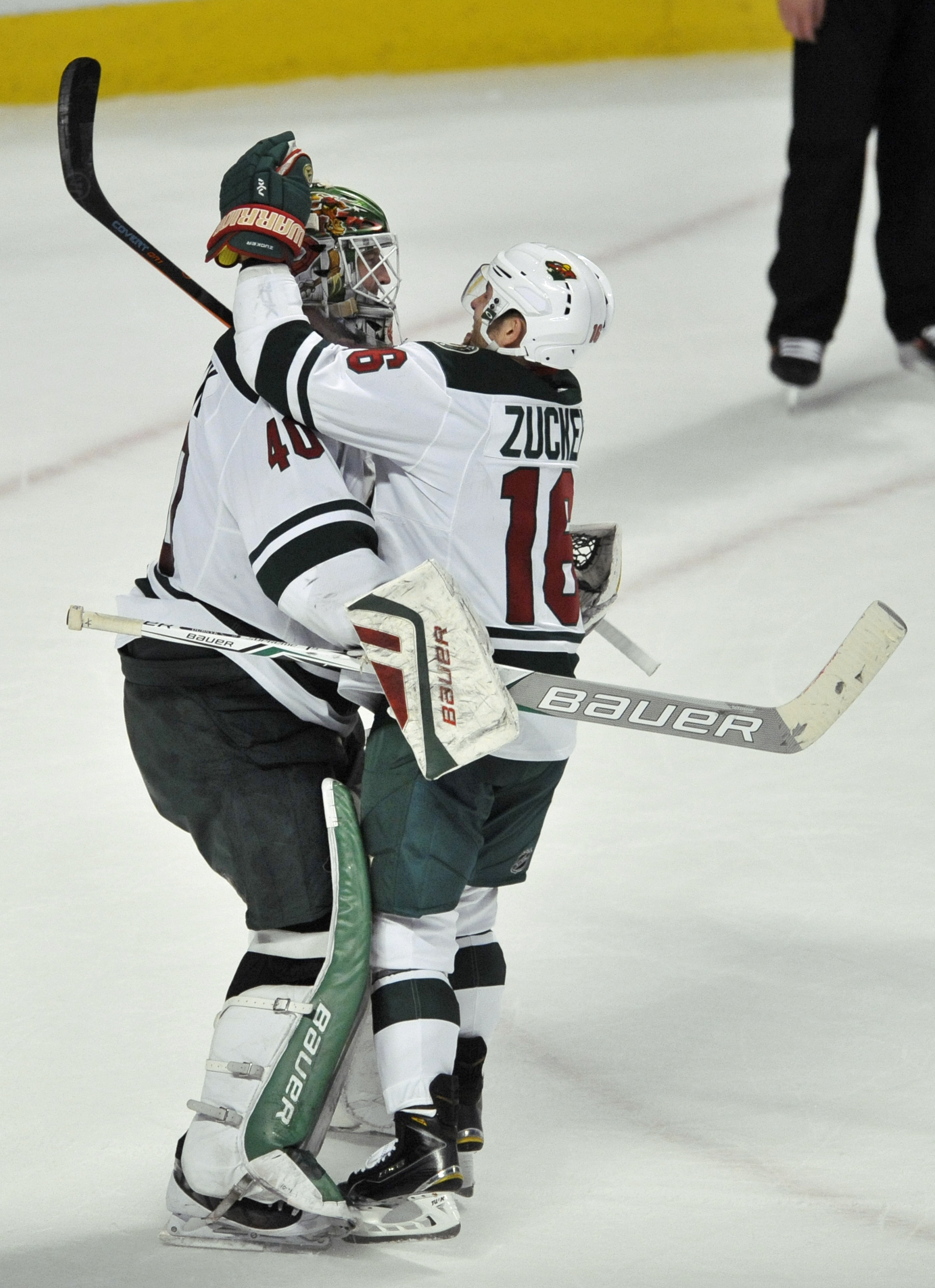 Minnesota Wild goalie Devan Dubnyk (40) celebrates with teammate Jason Zucker (16) after defeating the Chicago Blackhawks 3-2 in a shootout during an NHL hockey game Sunday, March 20, 2016, in Chicago. (AP Photo/Paul Beaty)