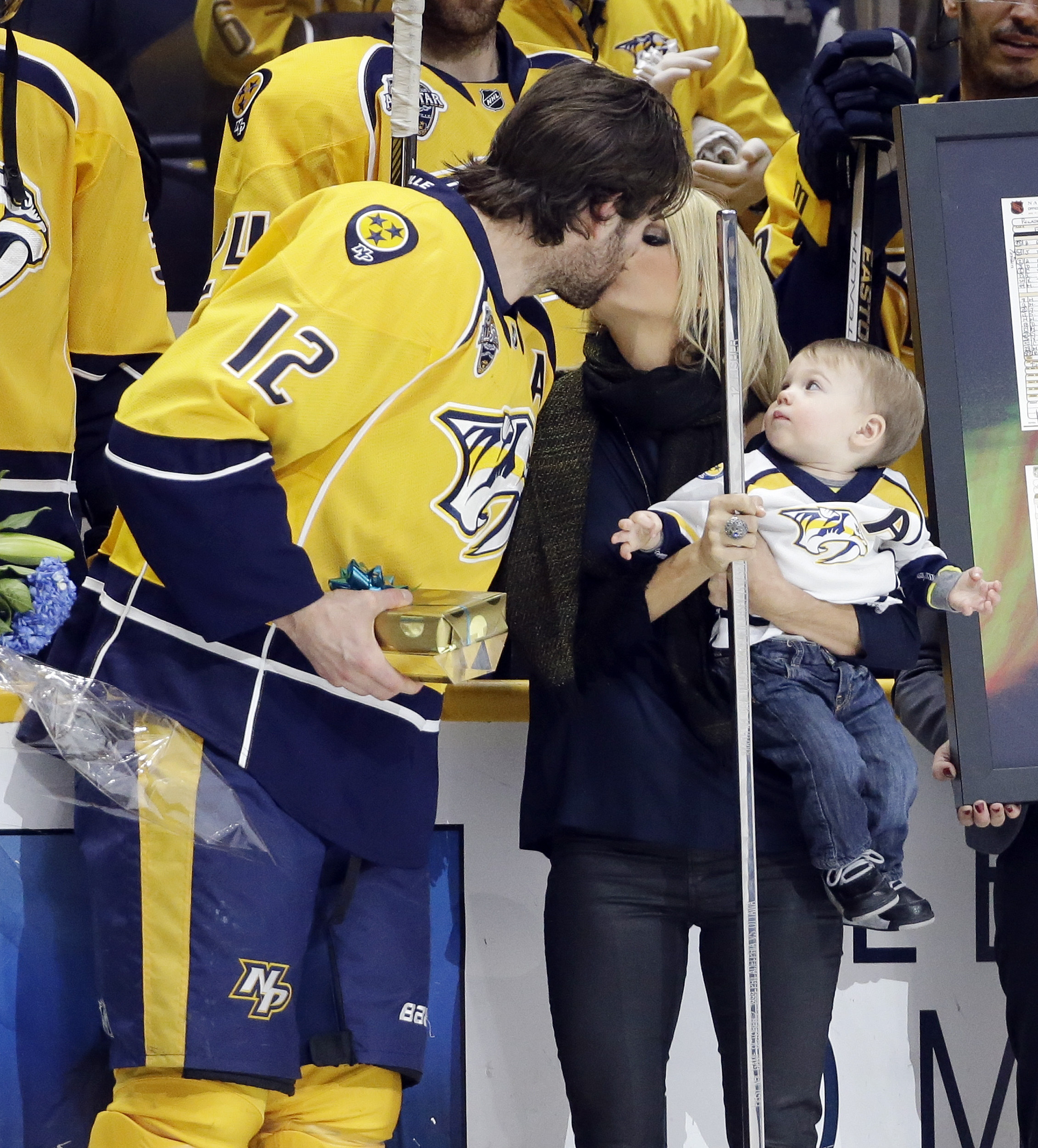 Nashville Predators forward Mike Fisher kisses his wife, singer Carrie Underwood, as Fisher is honored for his 1,000th NHL hockey game prior to playing against the Los Angeles Kings Monday, March 21, 2016, in Nashville, Tenn. Watching is their son, Isaiah