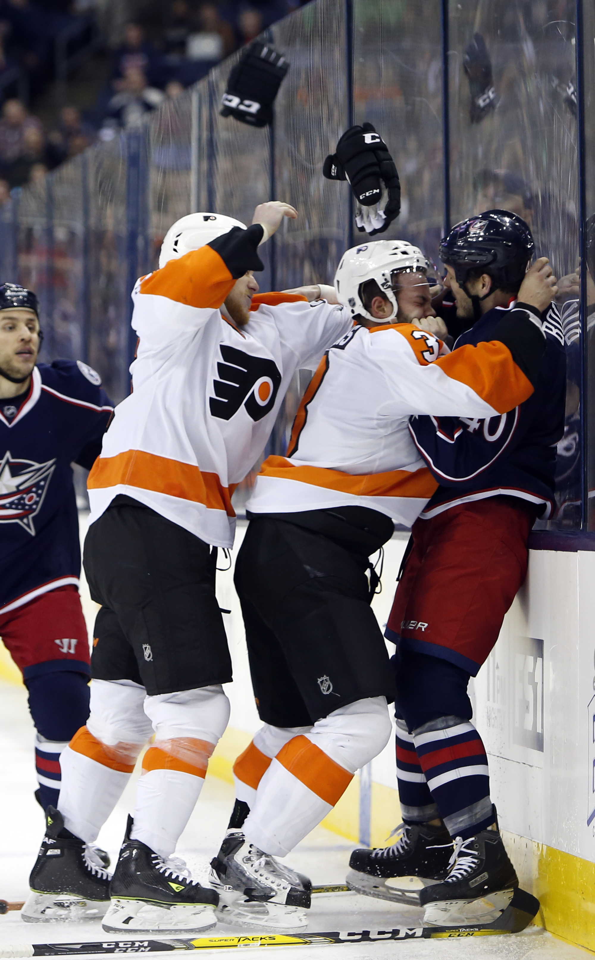 Philadelphia Flyers' Ryan White, left, and Radko Gudas, center, of the Czech Republic, attack Columbus Blue Jackets' Jared Boll after a hit by Boll during the second period of an NHL hockey game Tuesday, March 22, 2016, in Columbus, Ohio. (AP Photo/Jay La