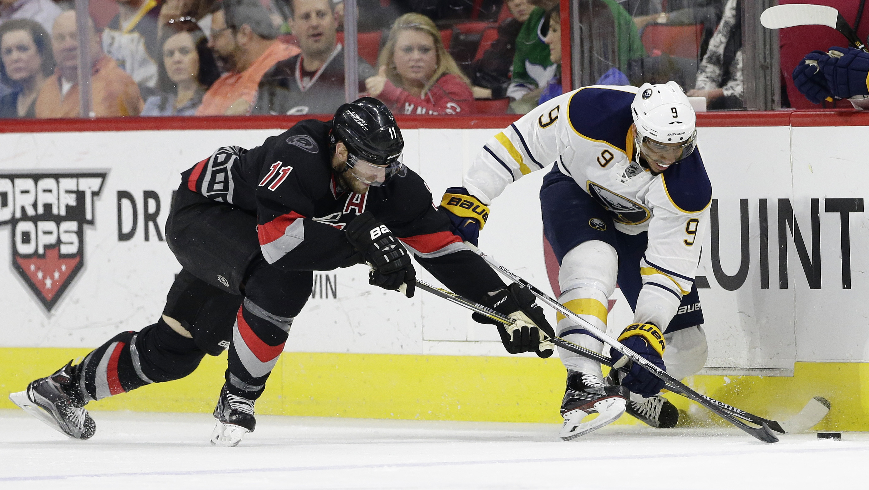 Buffalo Sabres' Evander Kane (9) and Carolina Hurricanes' Jordan Staal (11) chase the puck during the second period of an NHL hockey game in Raleigh, N.C., Tuesday, March 22, 2016. Buffalo won 3-2. (AP Photo/Gerry Broome)