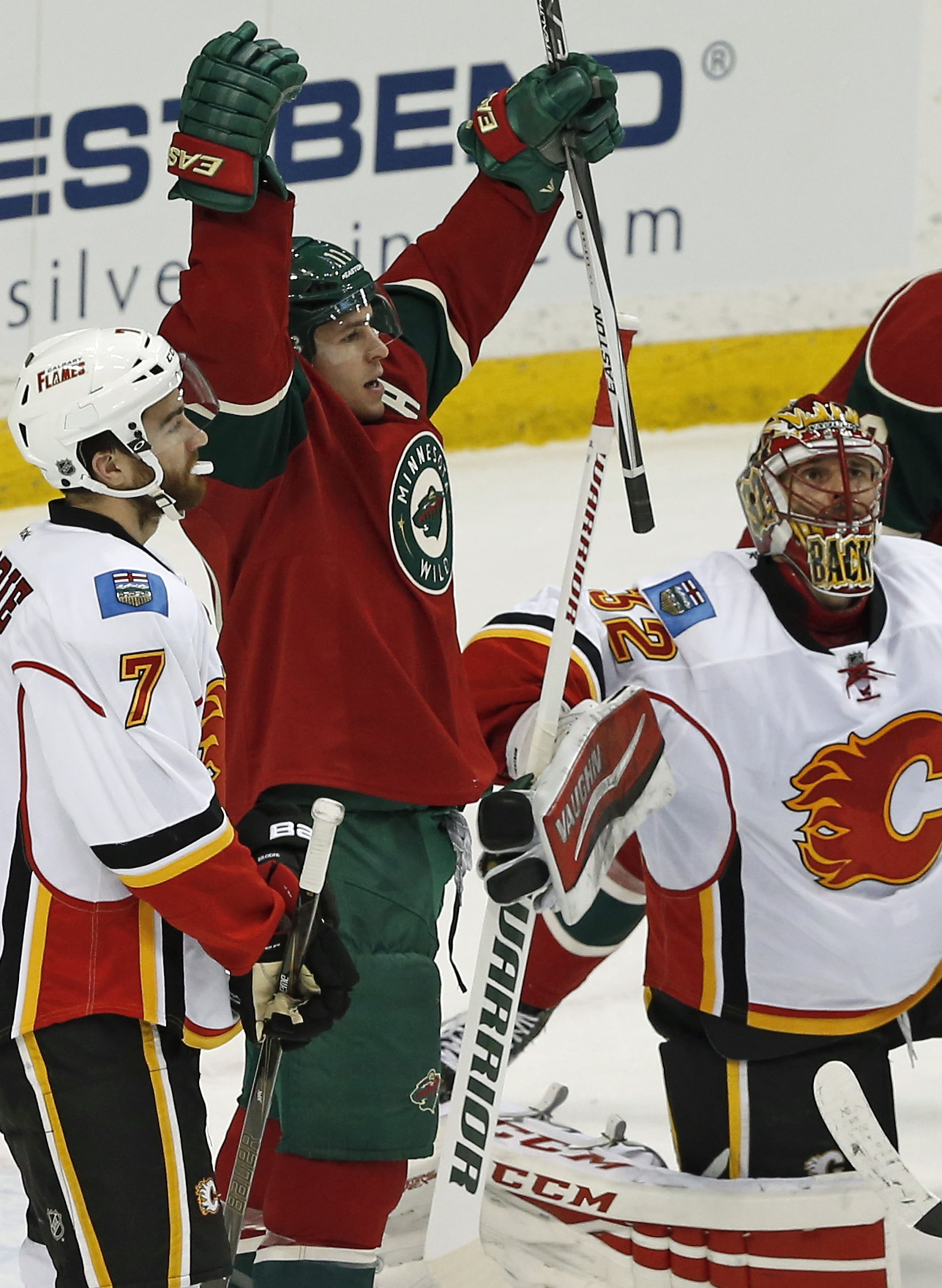 Minnesota Wilds Zach Parise, center, celebrates his third goal for the hat trick against Calgary Flames goalie Niklas Backstrom, right, of Finland in the first period of an NHL hockey game, Thursday, March 24, 2016, in St. Paul, Minn. (AP Photo/Jim Mone)
