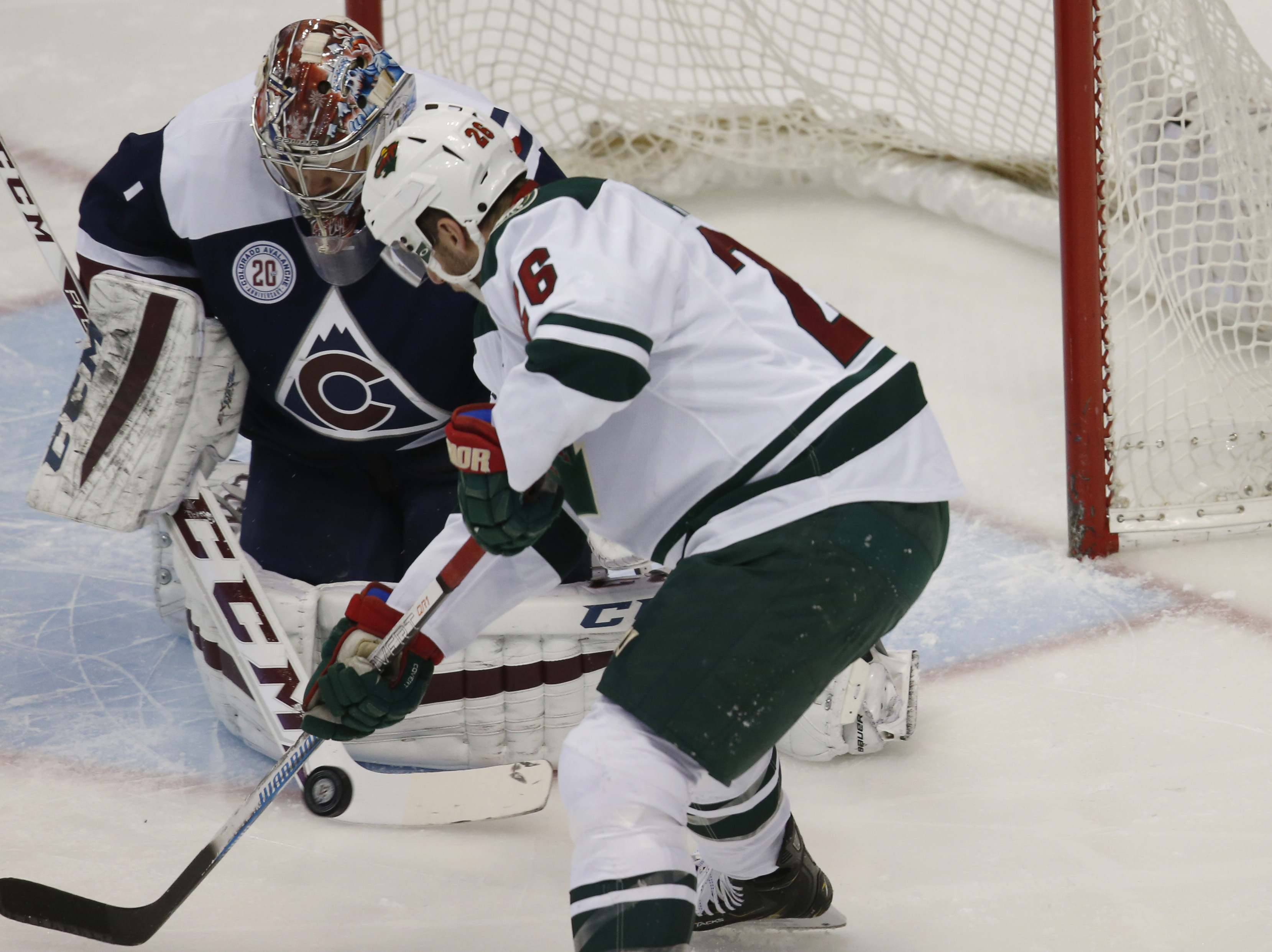 Minnesota Wild left wing Thomas Vanek, front, of Austria, directs a shot at Colorado Avalanche goalie Semyon Varlamov, of Russia, in the first period of an NHL hockey game Saturday, March 26, 2016, in Denver. (AP Photo/David Zalubowski)