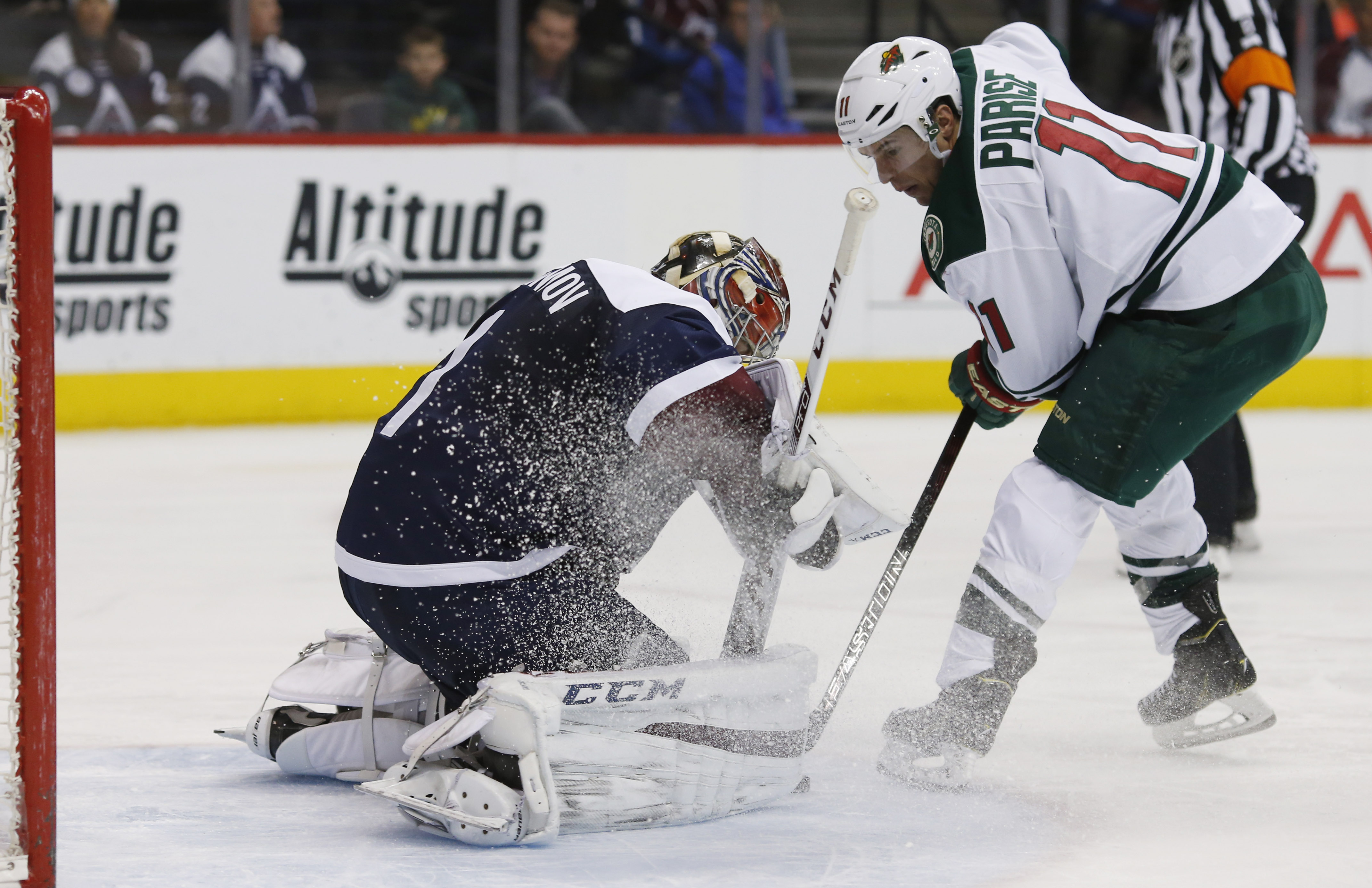 Minnesota Wild left wing Zach Parise, right, directs a shot at Colorado Avalanche goalie Semyon Varlamov, of Russia, in the second period of an NHL hockey game Saturday, March 26, 2016, in Denver. (AP Photo/David Zalubowski)