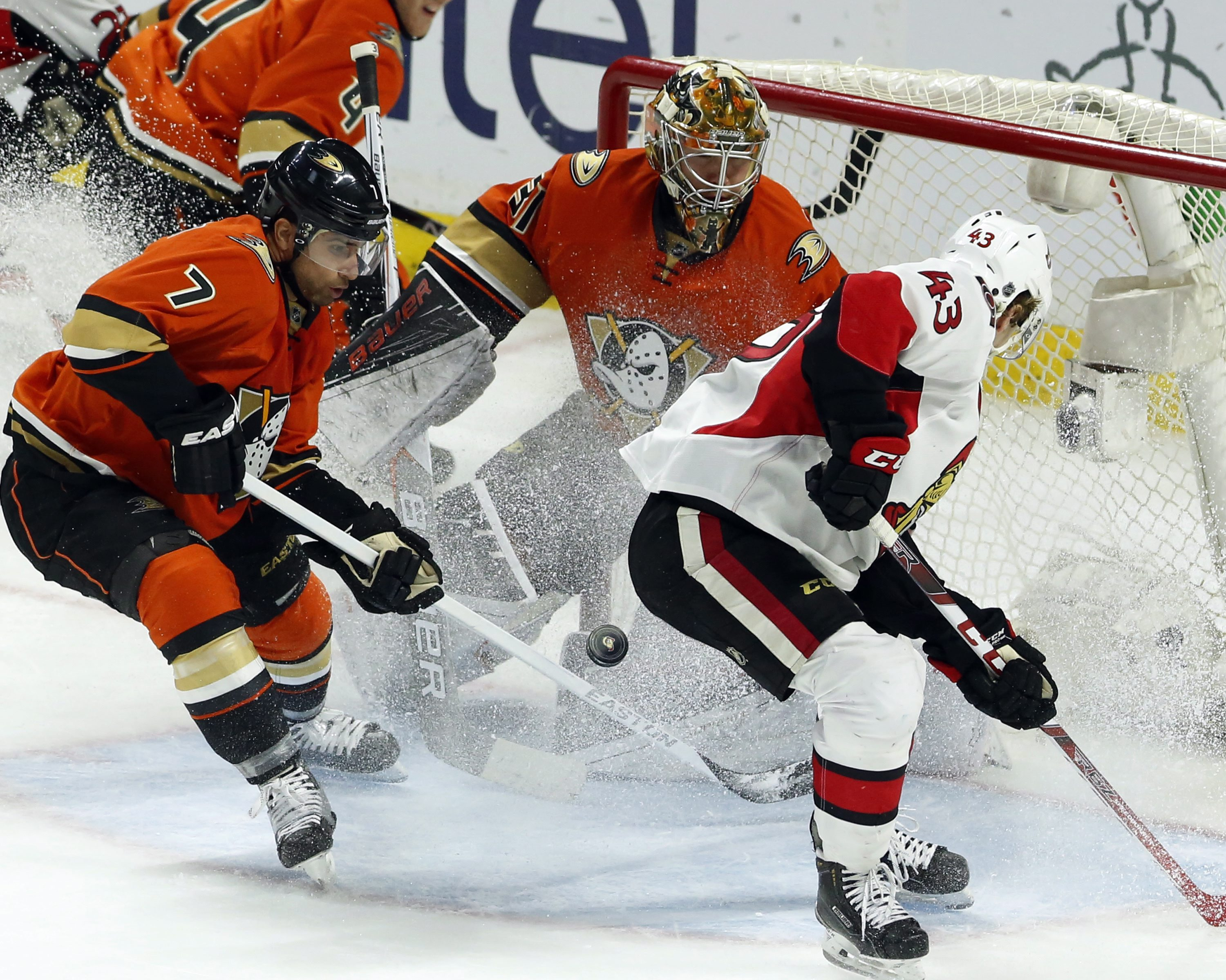 Ottawa Senators' Ryan Dzingel (43) and Anaheim Ducks' Andrew Cogliano (7) and Frederik Andersenn (31) try to gain control of a loose puck during the second period of an NHL hockey game Saturday, March 26, 2016, in Ottawa, Ontario. (Fred Chartrand/The Cana