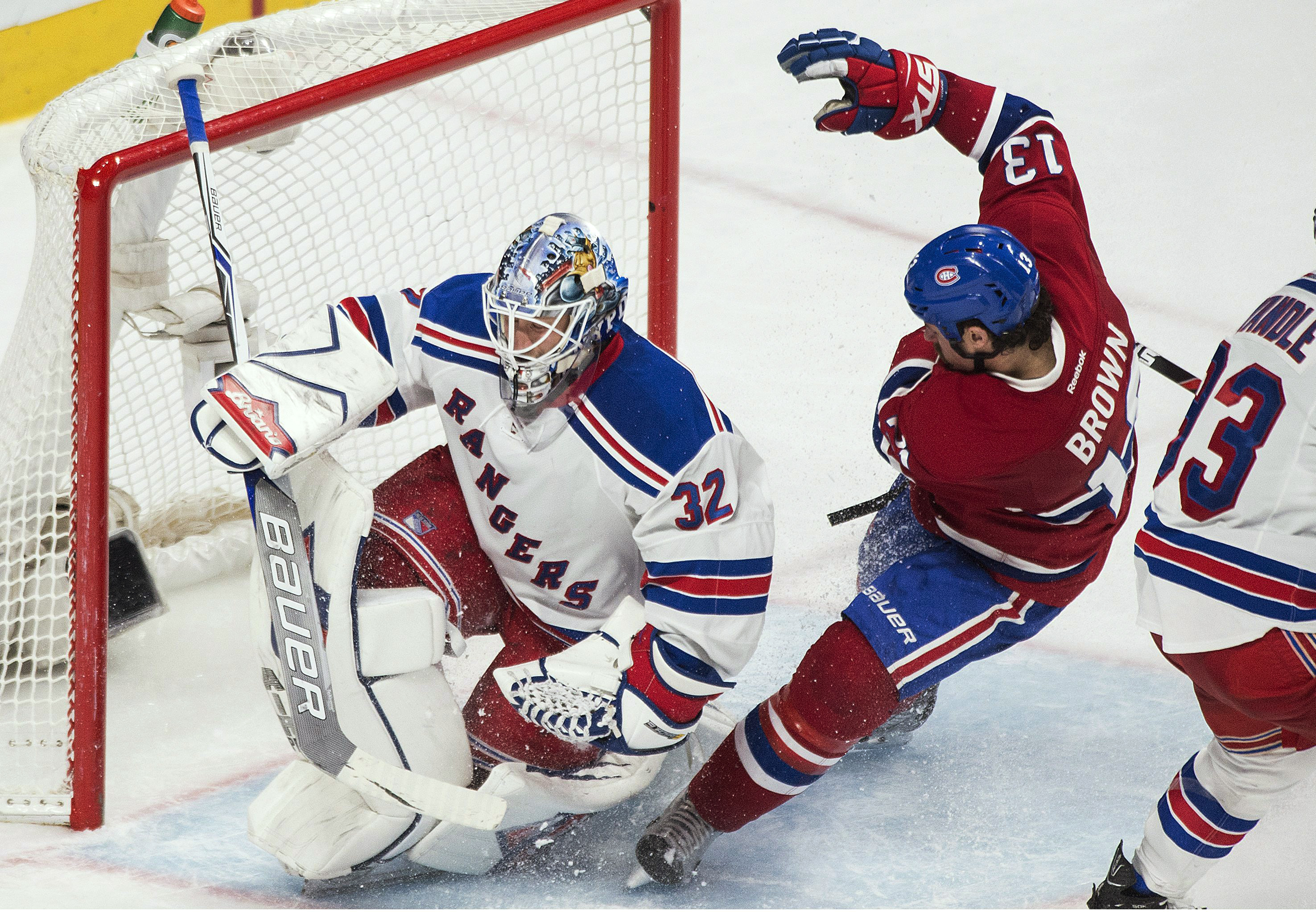 Montreal Canadiens' Mike Brown (13) slides in on New York Rangers goaltender Antti Raanta during the third period of an NHL hockey game in Montreal, Saturday, March 26, 2016. (Graham Hughes/The Canadian Press via AP)