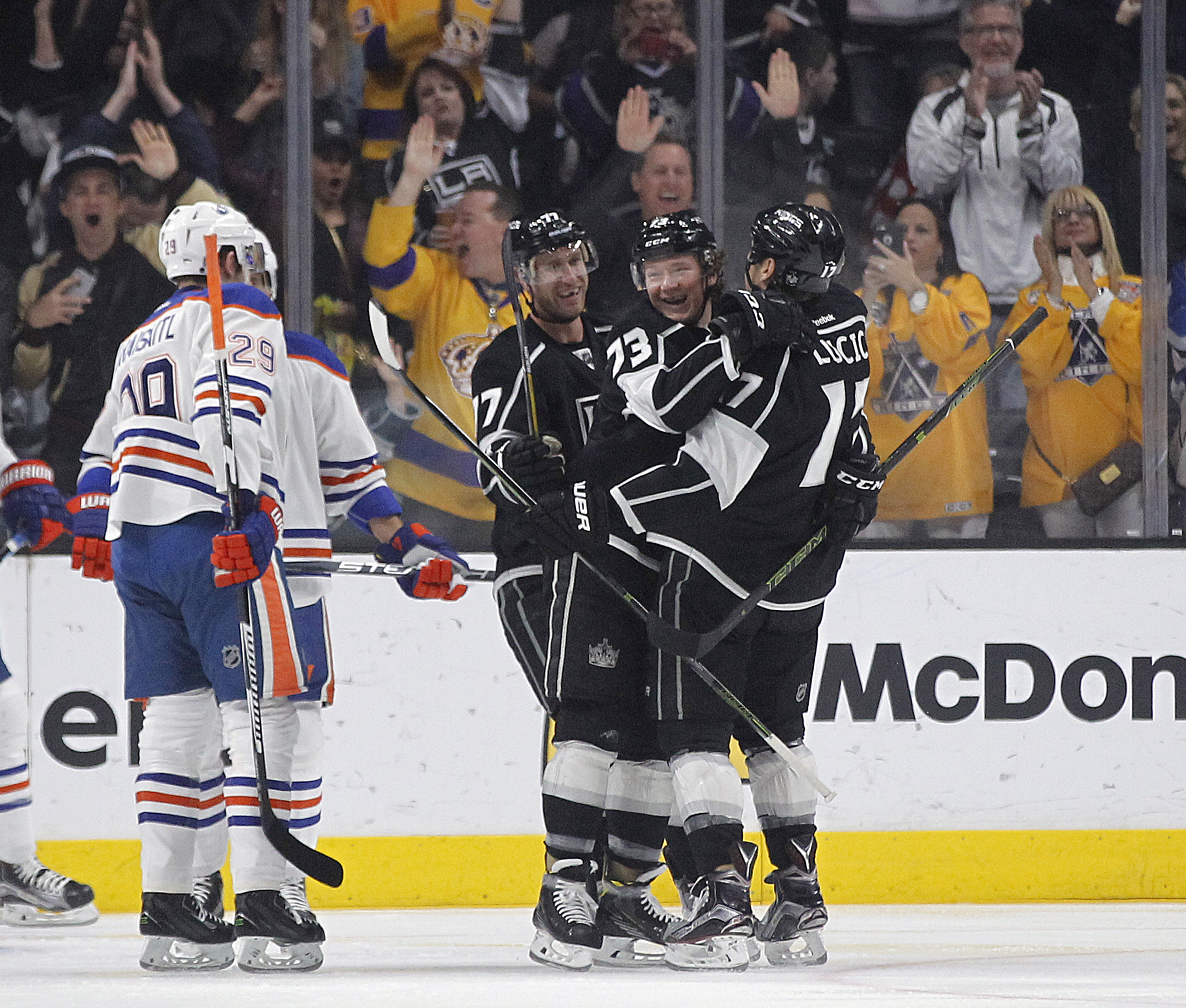 Los Angeles Kings center Tyler Toffoli (73) celebrates his goal with left wing Milan Lucic, right, and center Jeff Carter, as Edmonton Oilers center Leon Draisaitl (29), of Germany, skates by during the first period of an NHL hockey game in Los Angeles, S