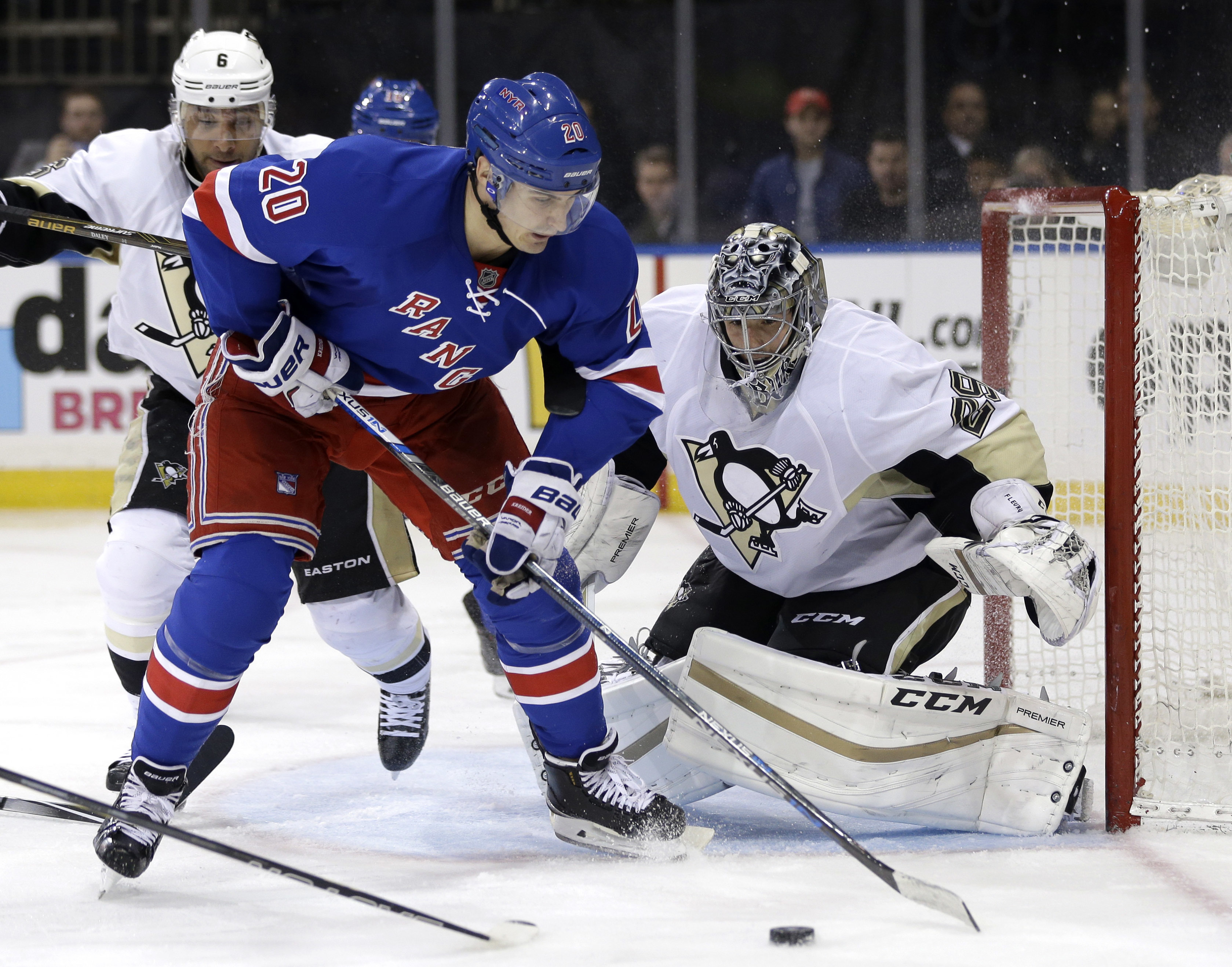 New York Rangers' Chris Kreider, left, moves the puck in front of Pittsburgh Penguins goalie Marc-Andre Fleury during the second period of the NHL hockey game, Sunday, March 27, 2016, in New York. (AP Photo/Seth Wenig)