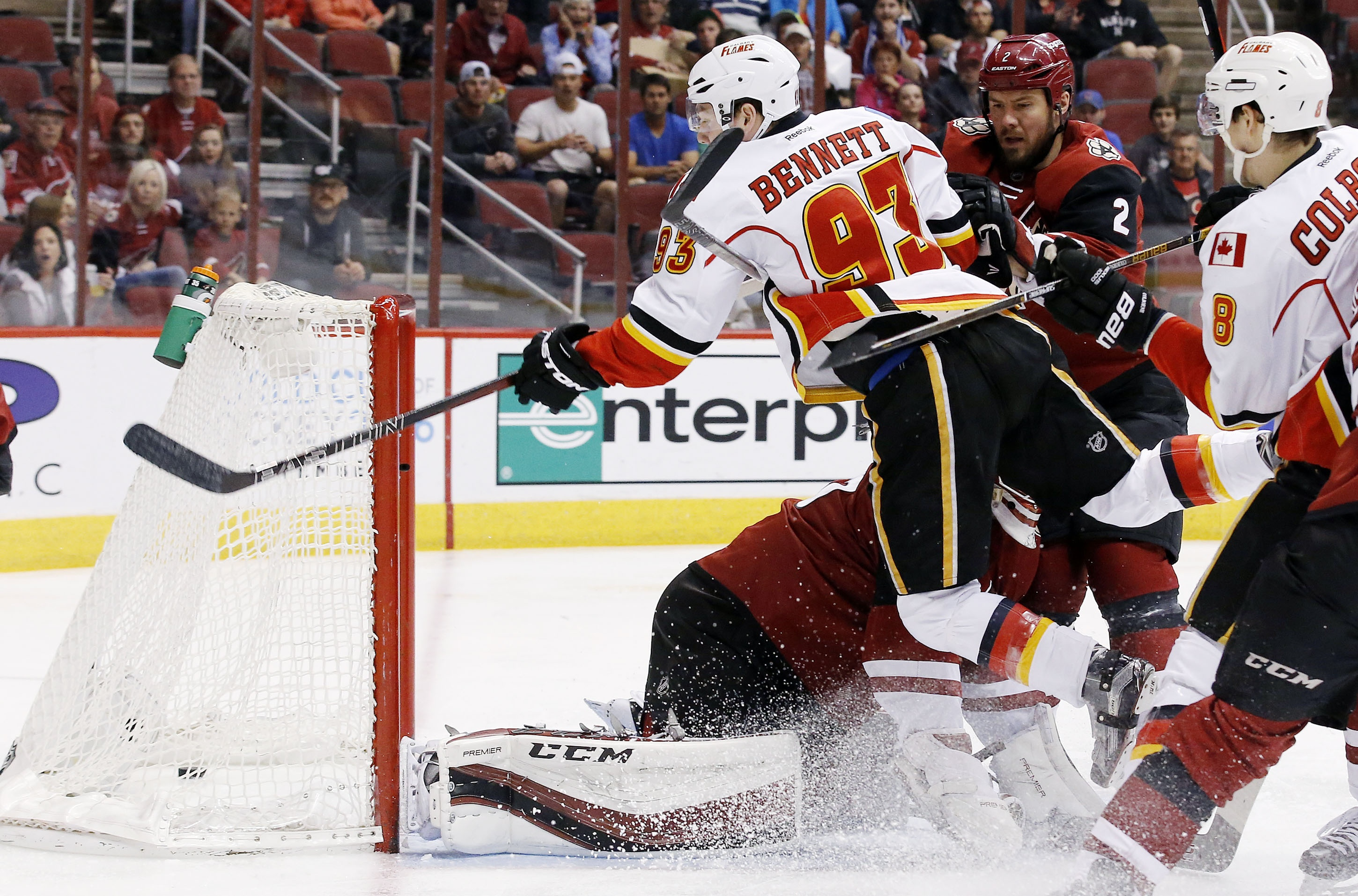 Calgary Flames' Sam Bennett (93) gets sent flying into the air by Arizona Coyotes' Nicklas Grossmann (2), of Sweden, but not before he sends the puck past Coyotes goalie Louis Domingue, bottom left, for a goal as Flames' Joe Colborne (8) watches during th