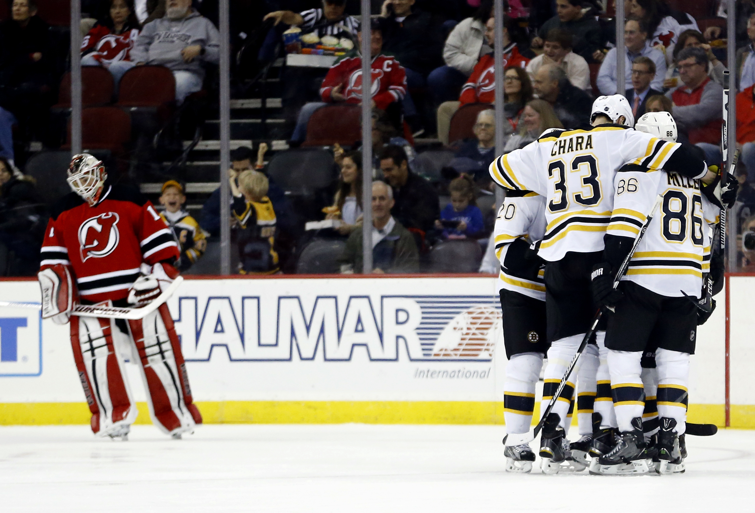 Boston Bruins, right, celebrate after Brad Marchand (63) scored a goal on New Jersey Devils goalie Keith Kinkaid, left, during the second period of an NHL hockey game, Tuesday, March 29, 2016, in Newark, N.J. (AP Photo/Julio Cortez)