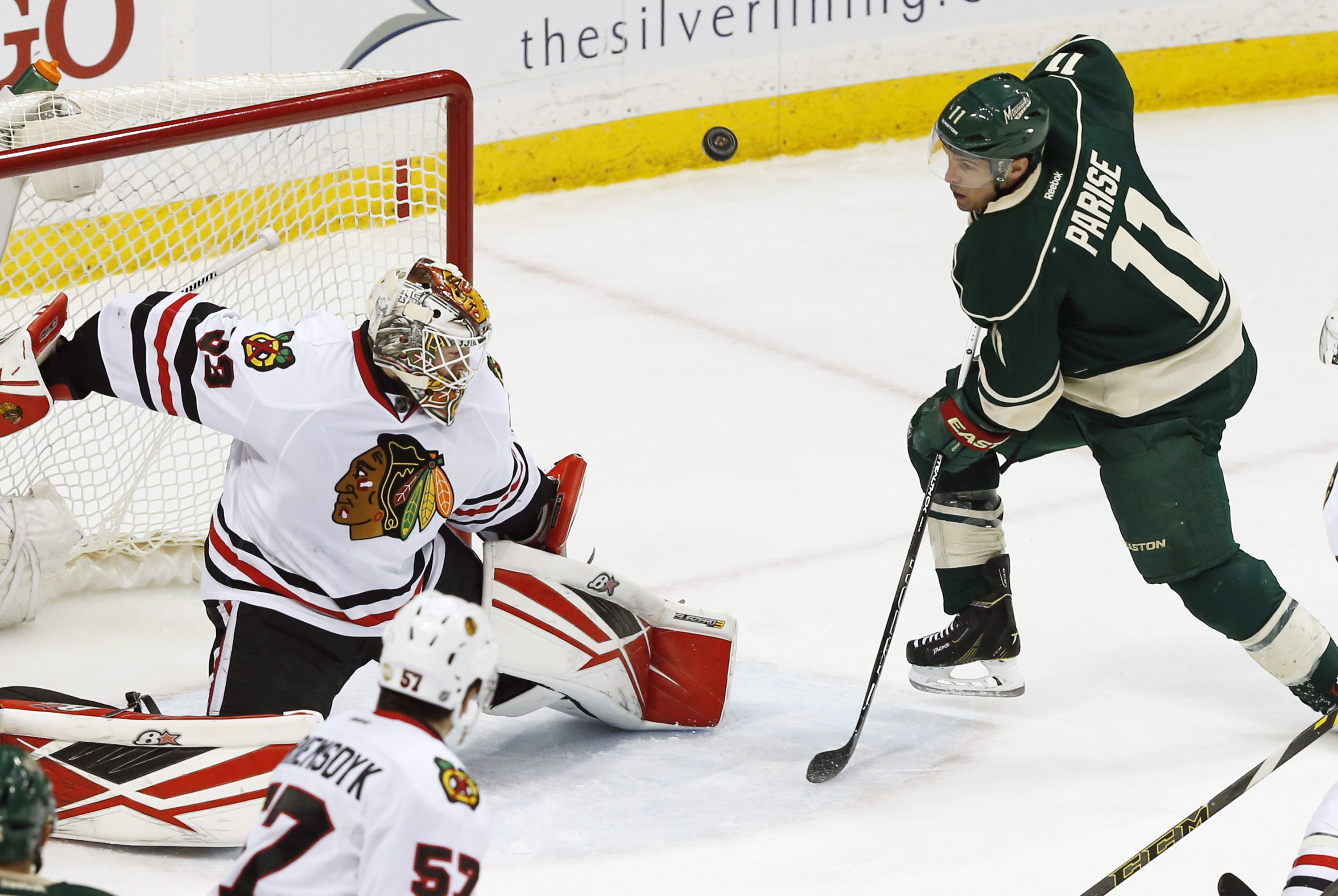 Chicago Blackhawks goalie Scott Darling, left, stops a shot by Minnesota Wilds Zach Parise, right, in the first period of an NHL hockey game Tuesday, March 29, 2016, in St. Paul, Minn. (AP Photo/Jim Mone)