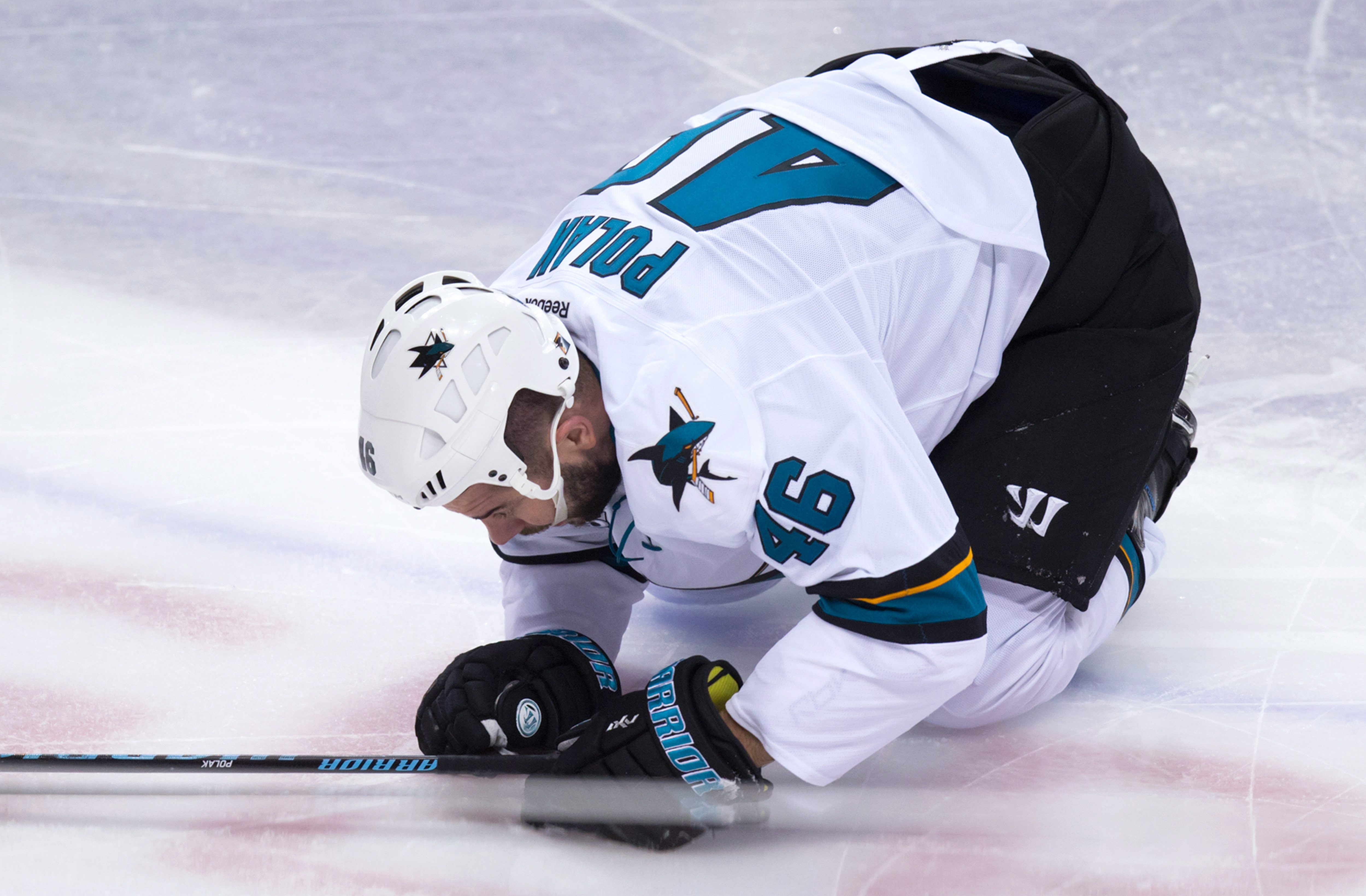 San Jose Sharks' Roman Polak, of the Czech Republic, kneels on the ice after being hit by Vancouver Canucks' Jake Virtanen during the second period of an NHL hockey game Tuesday, March 29, 2016, in Vancouver, British Columbia. (Darryl Dyck/The Canadian Pr