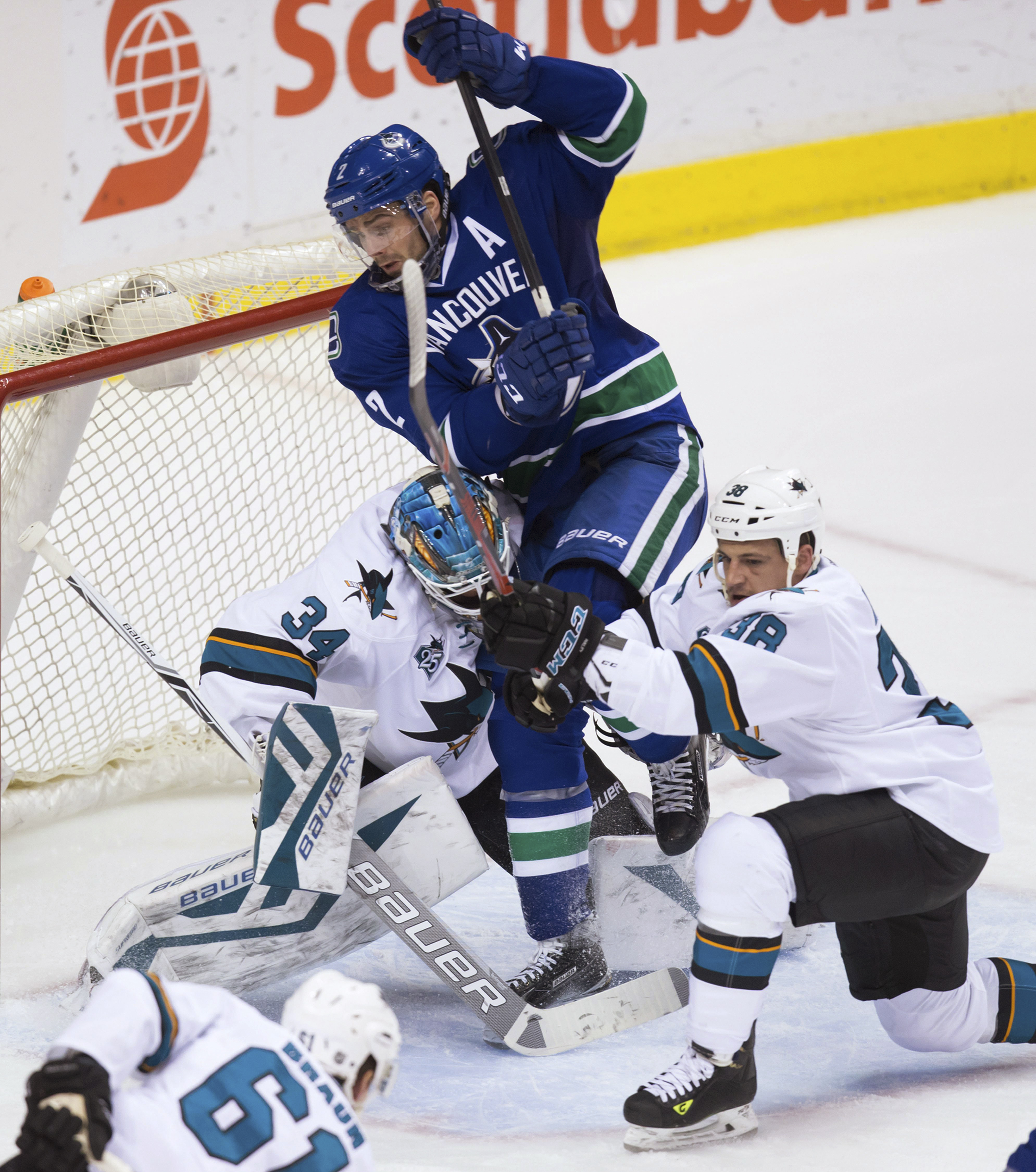 Vancouver Canucks' Dan Hamhuis, center, is checked into San Jose Sharks goalie James Reimer by Michael Haley, right, during the third period of an NHL hockey game Tuesday, March 29, 2016, in Vancouver, British Columbia. (Darryl Dyck/The Canadian Press via