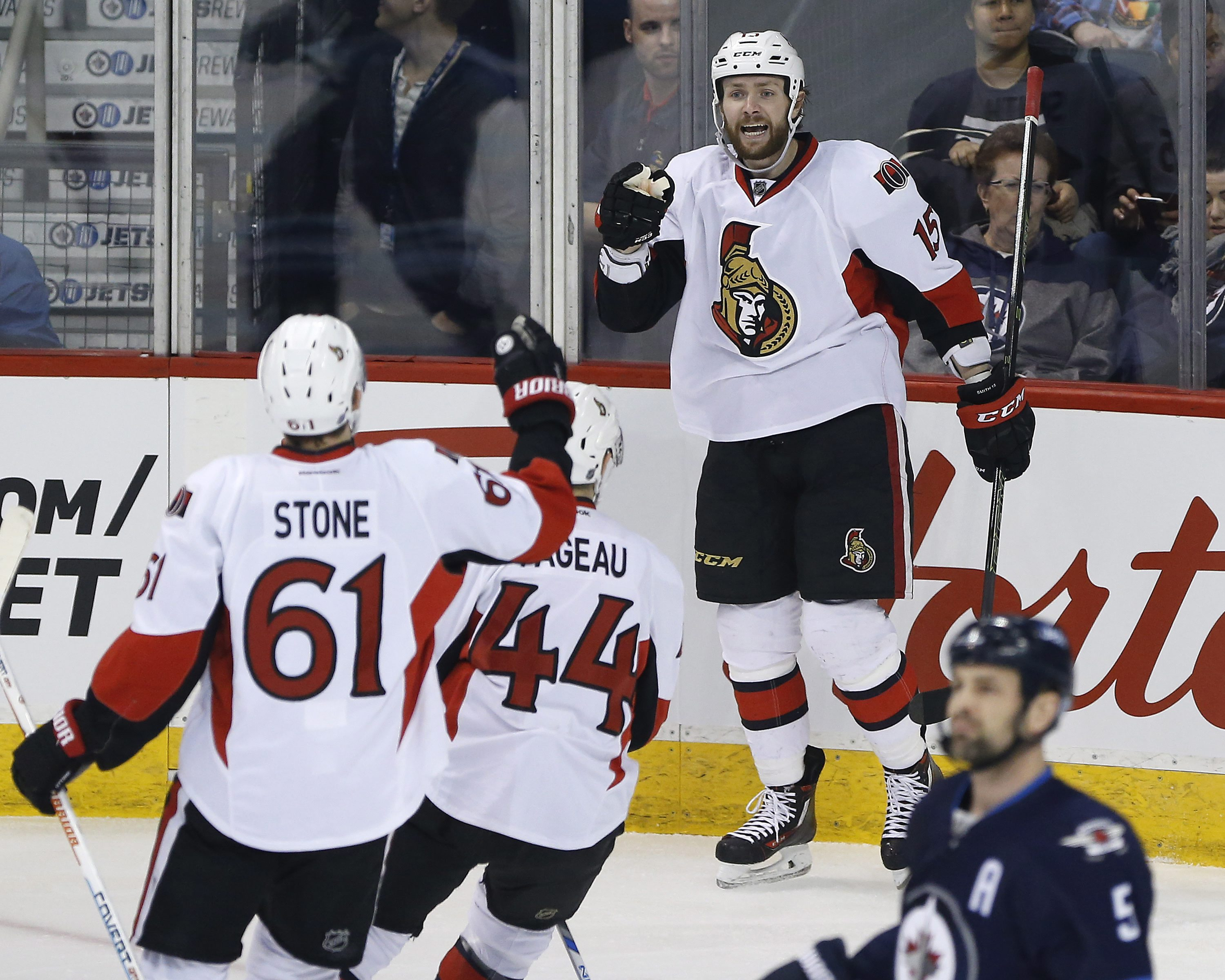 Ottawa Senators' Mark Stone (61), Jean-Gabriel Pageau (44) and Zack Smith (15) celebrate Smith's goal against the Winnipeg Jets during the first period of an NHL hockey game Tuesday, March 30, 2016, in Winnipeg, Manitoba. (John Woods/The Canadian Press vi