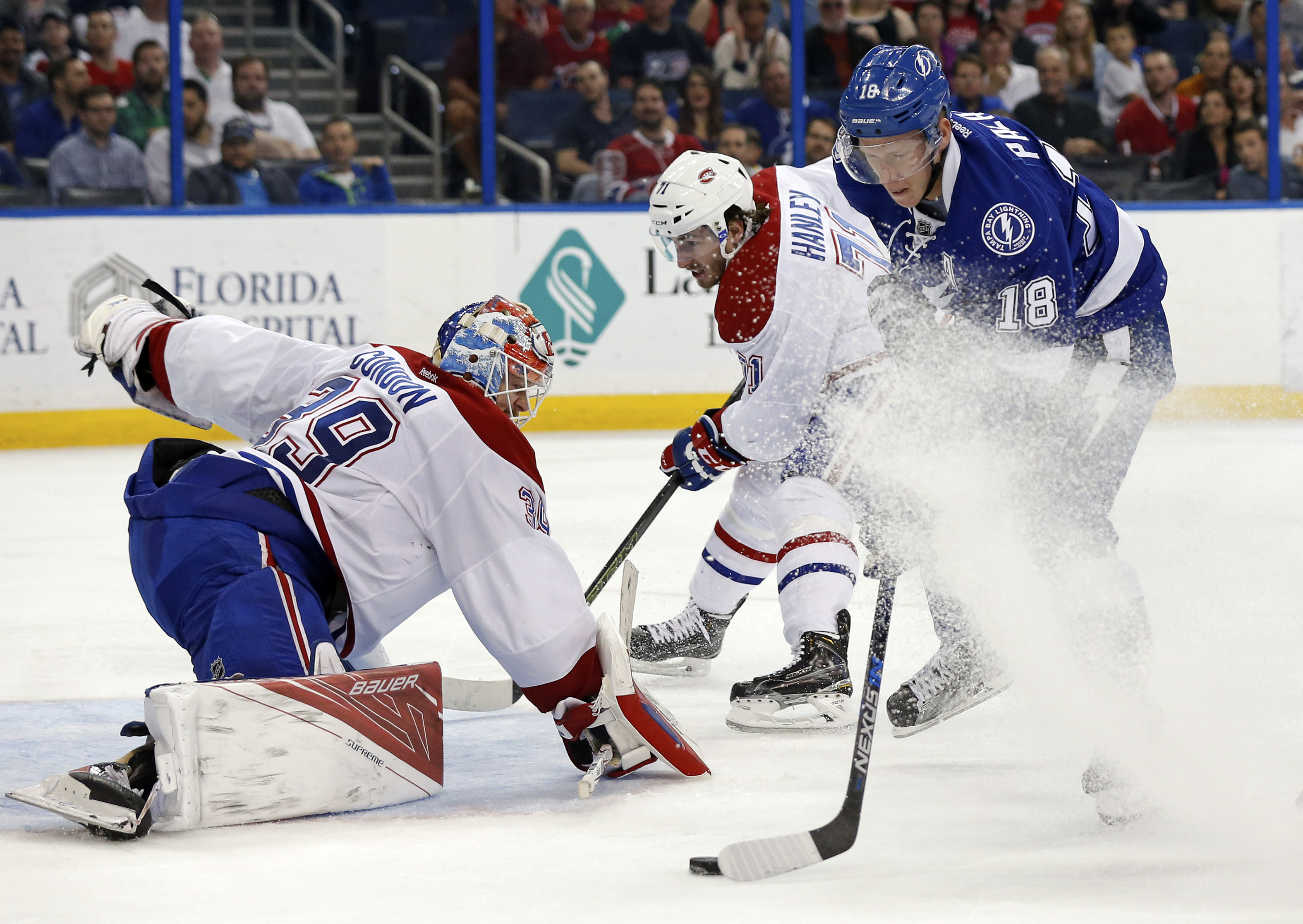 Tampa Bay Lightning's Ondrej Palat (18), of the Czech Republic, shoots on Montreal Canadiens goalie Mike Condon as Joel Hanley defends during the second period of an NHL hockey game Thursday, March 31, 2016, in Tampa, Fla. Palat was hooked by Hanley on th