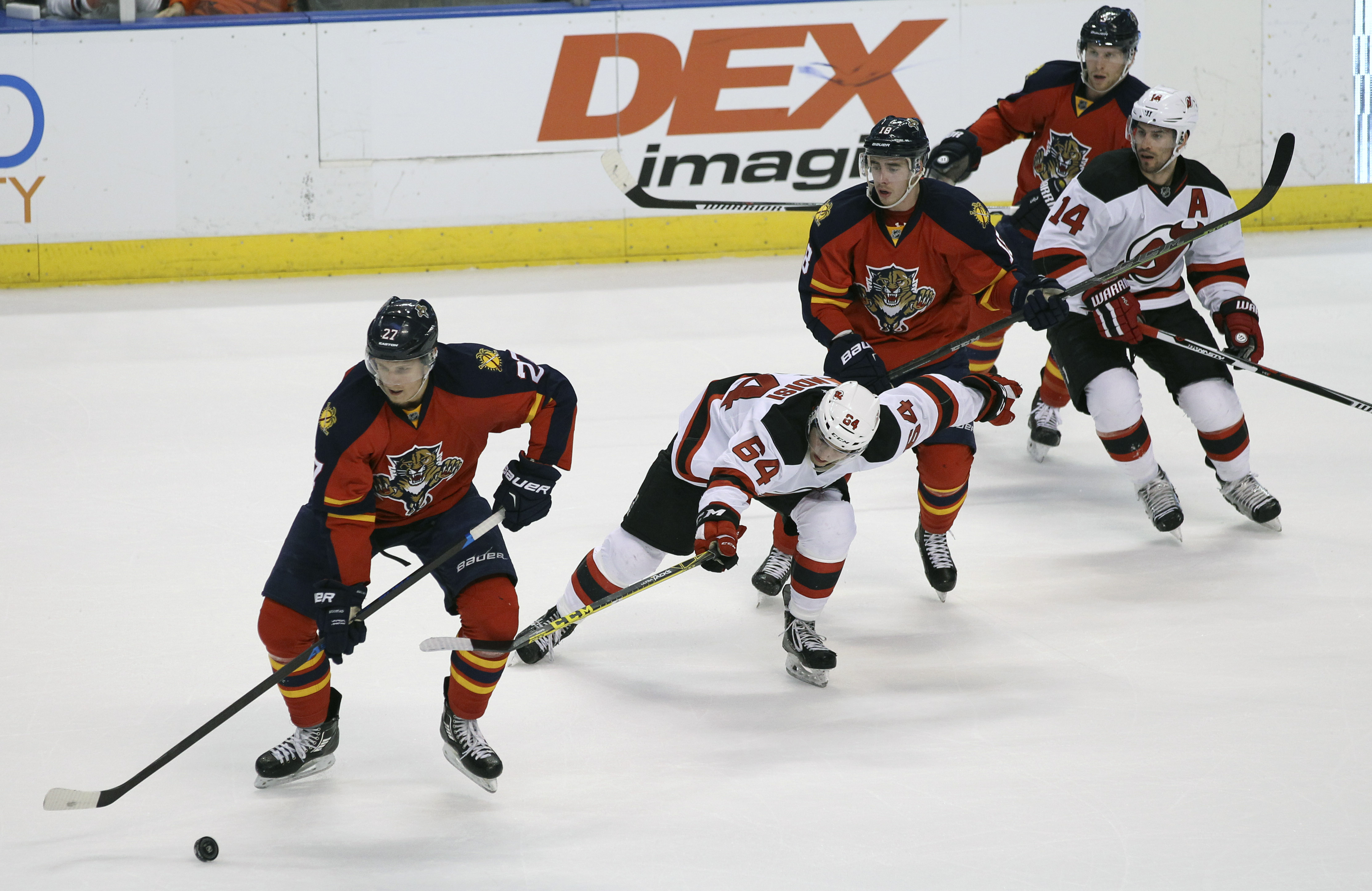 Florida Panthers Nick Bjugstad, left, moves the puck as New Jersey Devils' Joseph Blandisi (64) defends during the first period of an NHL hockey game, Thursday, March 31, 2016, in Sunrise, Fla. (AP Photo/Luis M. Alvarez)