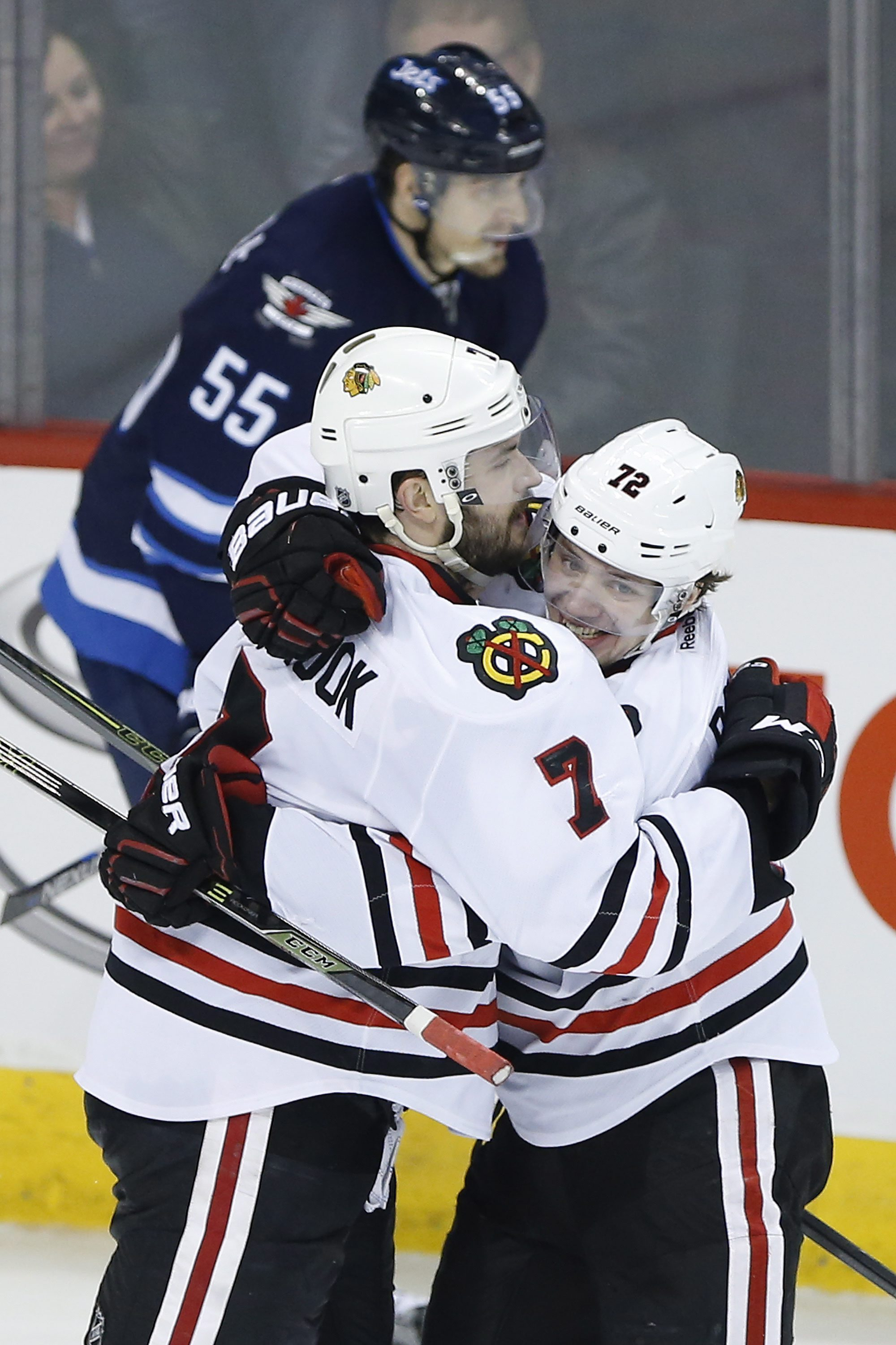 Chicago Blackhawks' Artemi Panarin (72) and Brent Seabrook (7) celebrate Seabrook's game-winning goal against the Winnipeg Jets during overtime in an NHL hockey game Friday, April 1, 2016, in Winnipeg, Manitoba. (John Woods/The Canadian Press via AP)
