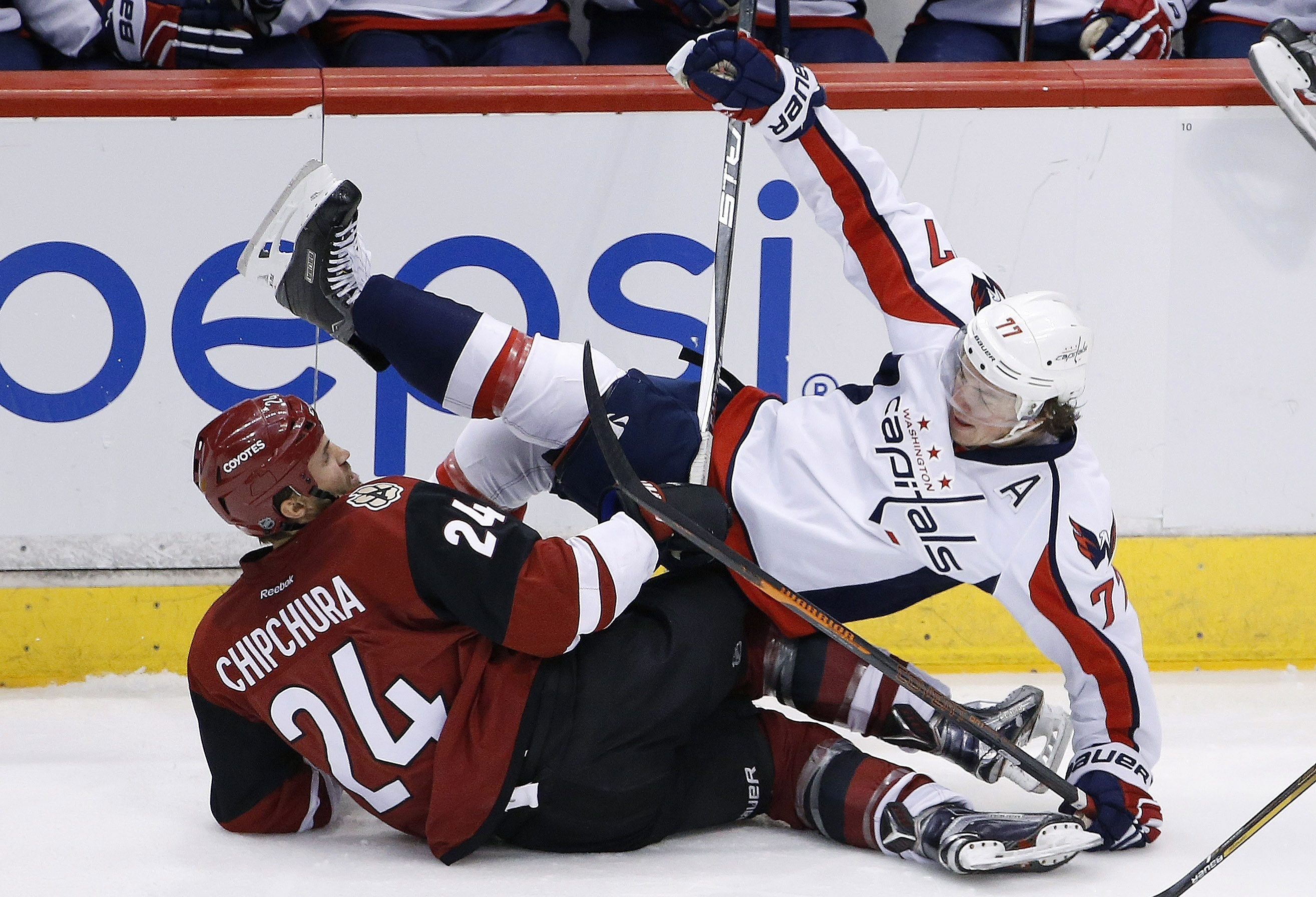Washington Capitals' T.J. Oshie (77) falls over Arizona Coyotes' Kyle Chipchura (24) during the third period of an NHL hockey game Saturday, April 2, 2016, in Glendale, Ariz. The Coyotes defeated the Capitals 3-0. (AP Photo/Ross D. Franklin)