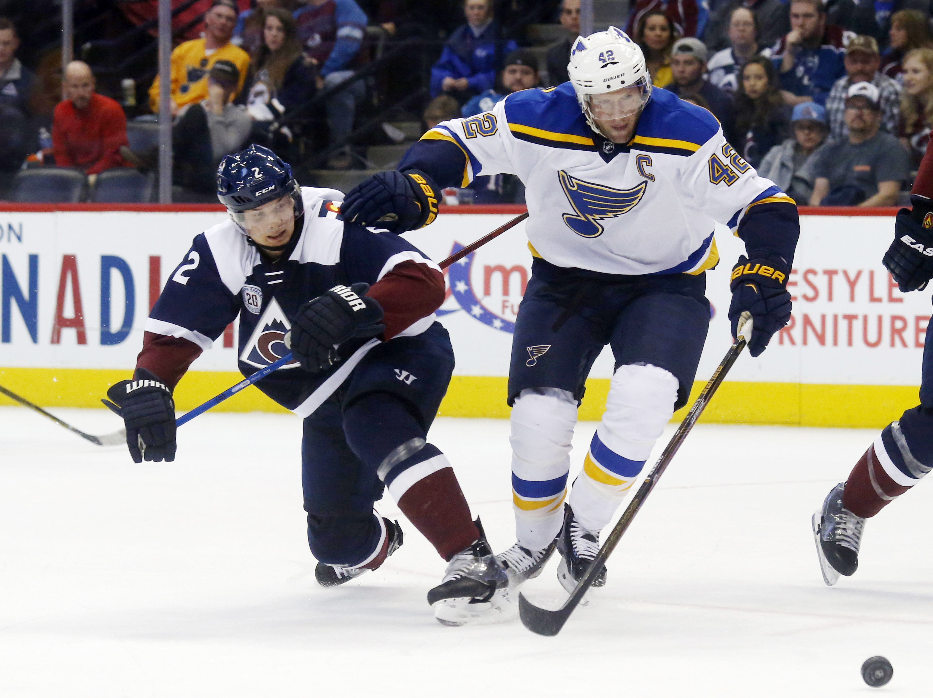 St. Louis Blues center David Backes, right, fights for control of the puck with Colorado Avalanche defenseman Nick Holden in the third period of an NHL hockey game Sunday, April 3, 2016, in Denver. St. Louis won 5-1. (AP Photo/David Zalubowski)