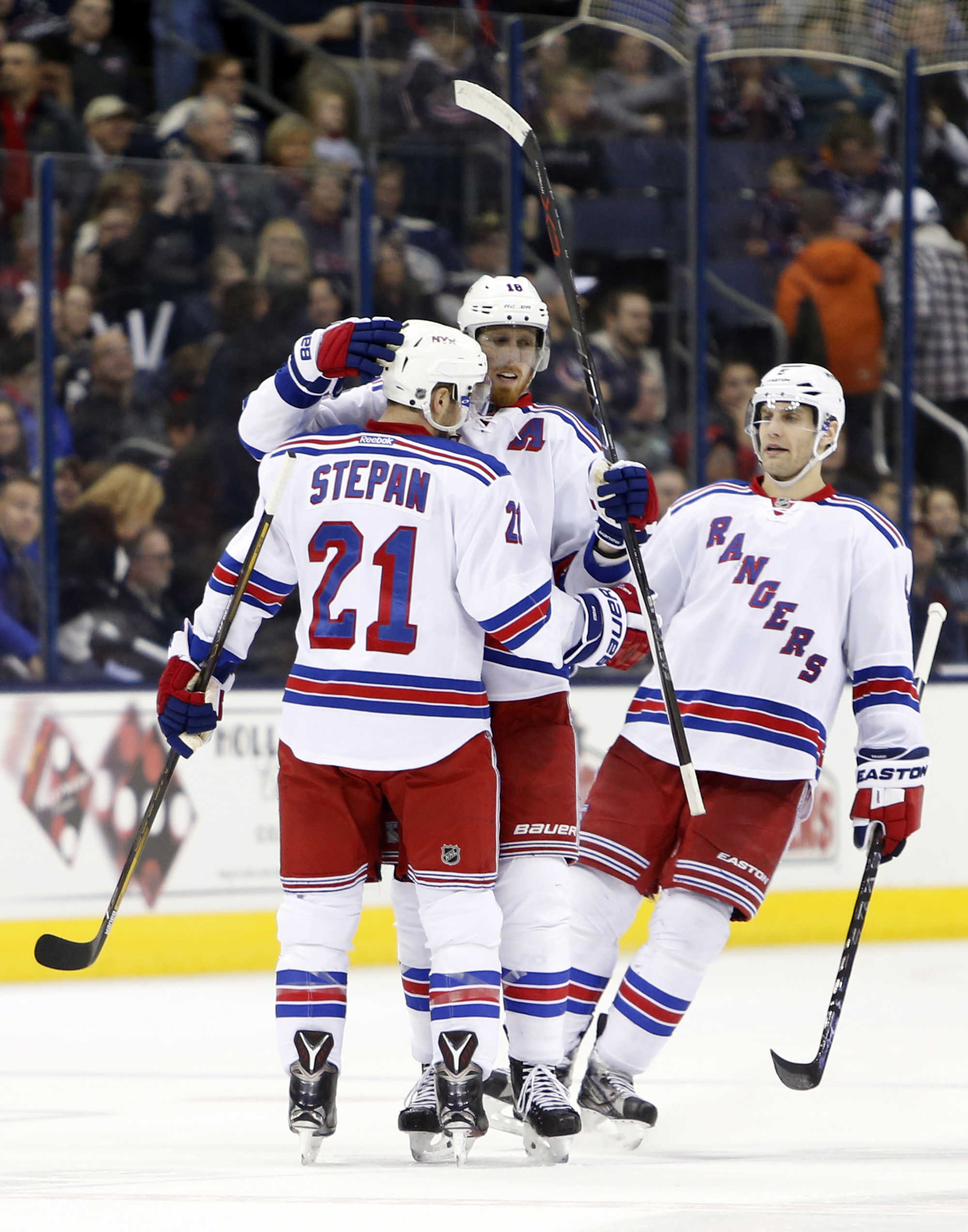 New York Rangers' Derek Stepan, left, is congratulated on his goal against the Columbus Blue Jackets by teammates Marc Staal, center, and Dan Girardi during the third period of an NHL hockey game Monday, April 4, 2016, in Columbus, Ohio. The Rangers beat