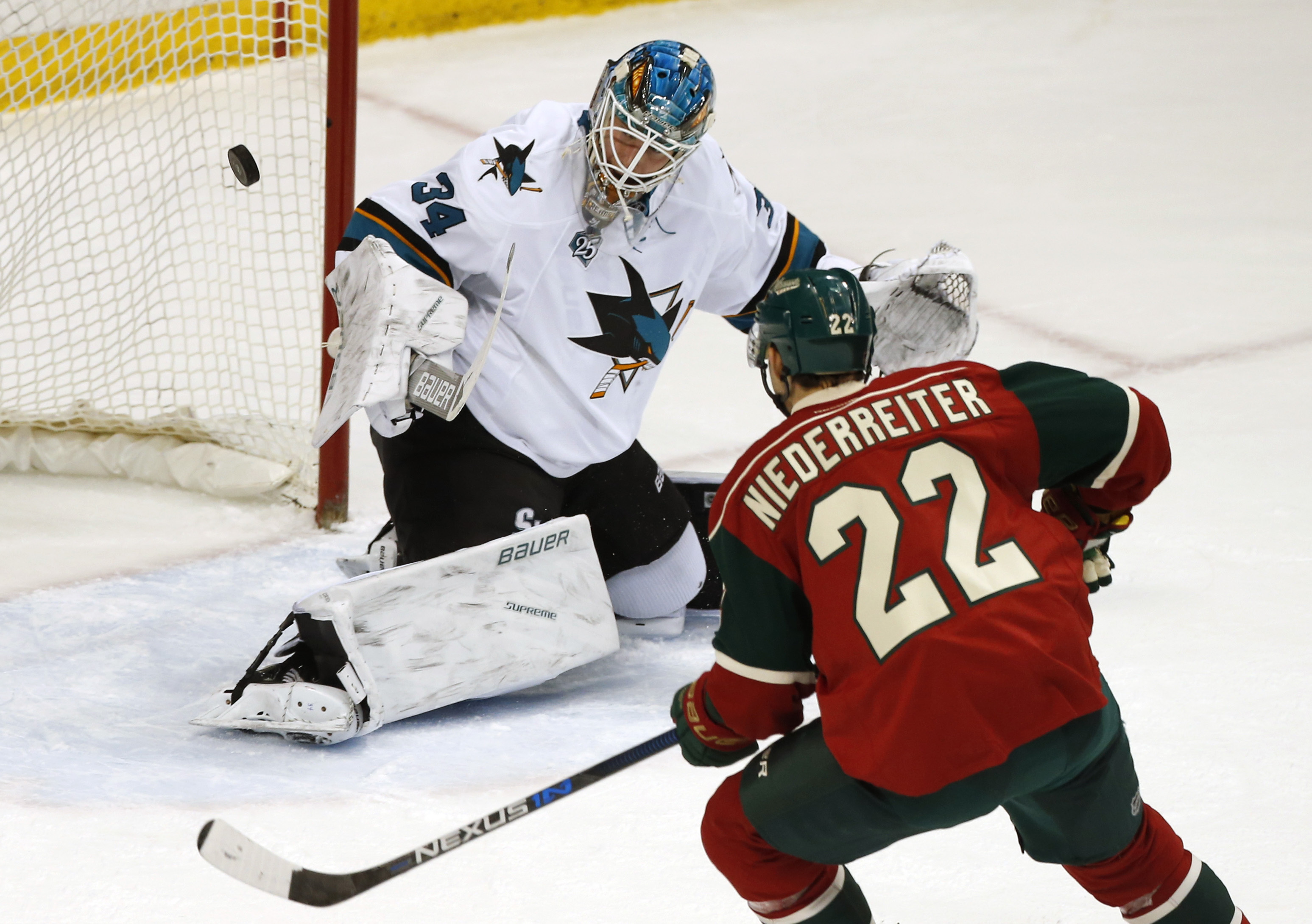 Minnesota Wild's Nino Niederreiter, right, of Switzerland, positions himself fora rebound as San Jose Sharks goalie James Reimer stops a shot in the first period of an NHL hockey game Tuesday, April 5, 2016, in St. Paul, Minn. (AP Photo/Jim Mone)