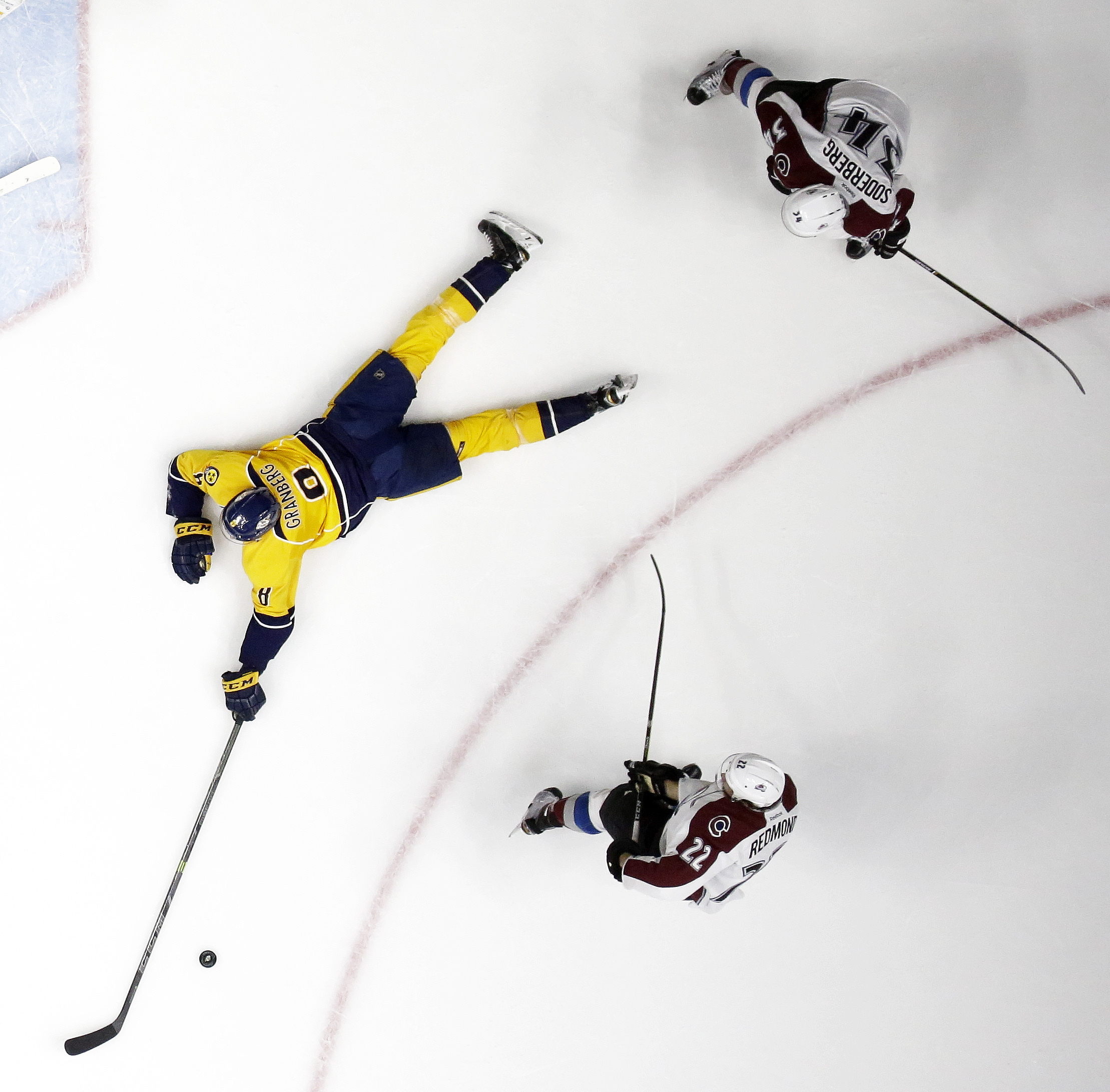 Nashville Predators' Peter Granberg (8), of Sweden, reaches for the puck as he defends Colorado Avalanche's Zach Redmond (22) and Carl Soderberg (34), of Sweden, during the second period of an NHL hockey game Tuesday, April 5, 2016, in Nashville, Tenn. (A