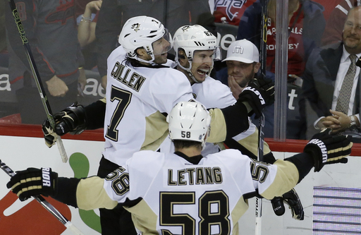Pittsburgh Penguins centers Matt Cullen (7) and Sidney Crosby (87) celebrate Crosby's winning goal with defenseman Kris Letang (58) after the overtime period of an NHL hockey game against the Washington Capitals, Thursday, April 7, 2016, in Washington. (A