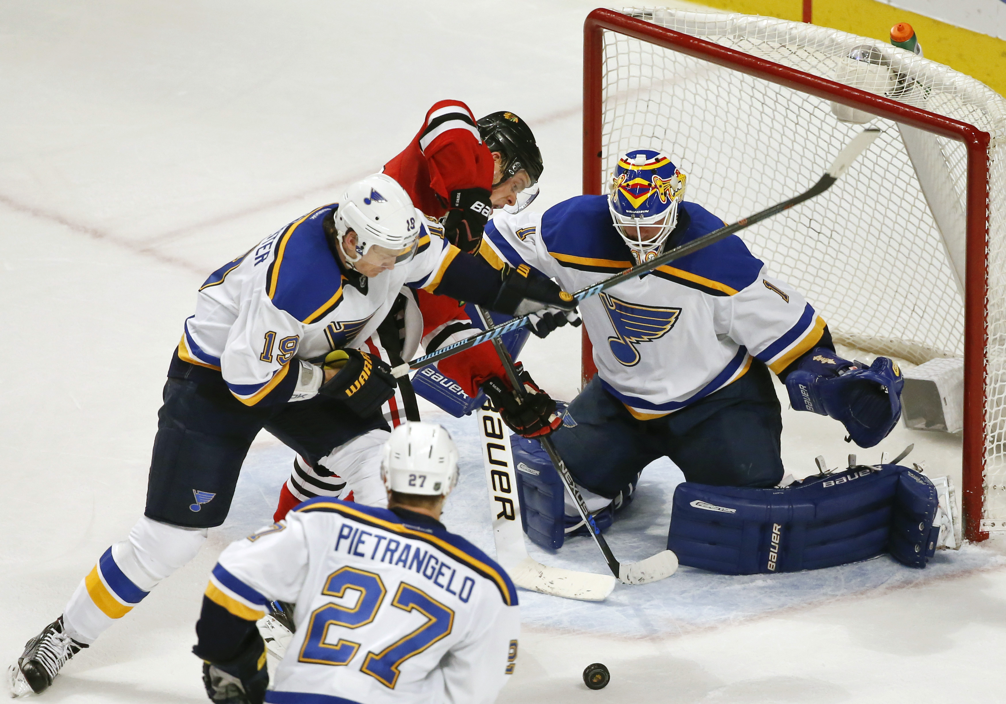 Chicago Blackhawks center Jonathan Toews, center, tries to score against St. Louis Blues goalie Brian Elliott, right, and defenseman Jay Bouwmeester, left, during the second period of an NHL hockey game Thursday, April 7, 2016, in Chicago. (AP Photo/Kamil