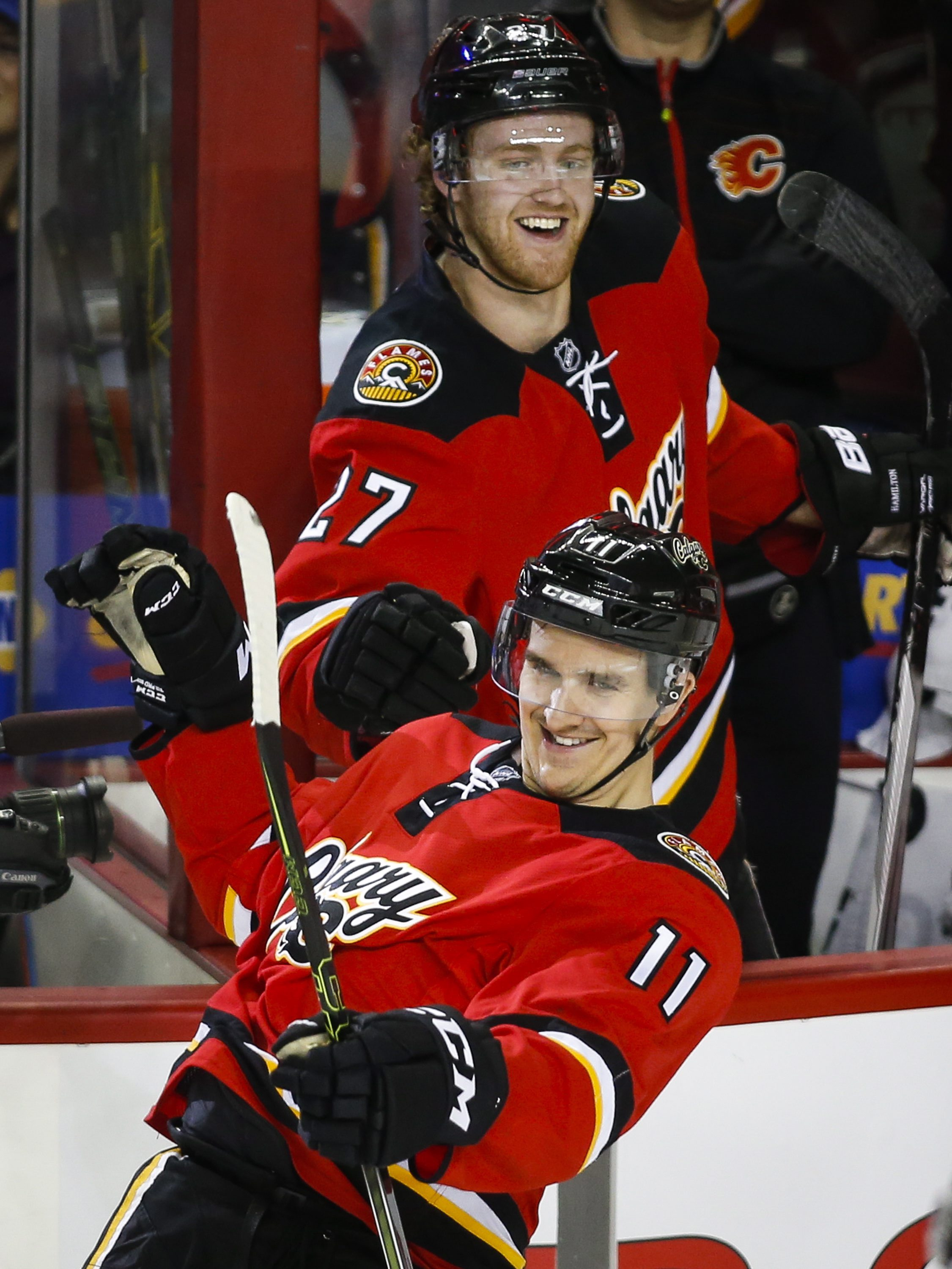 Calgary Flames' Mikael Backlund, right, from Sweden, is congratulated on his hat trick by teammate Dougie Hamilton during the second period of an NHL hockey game against the Vancouver Canucks on Thursday, April 7, 2016, in Calgary, Alberta. (Jeff McIntosh
