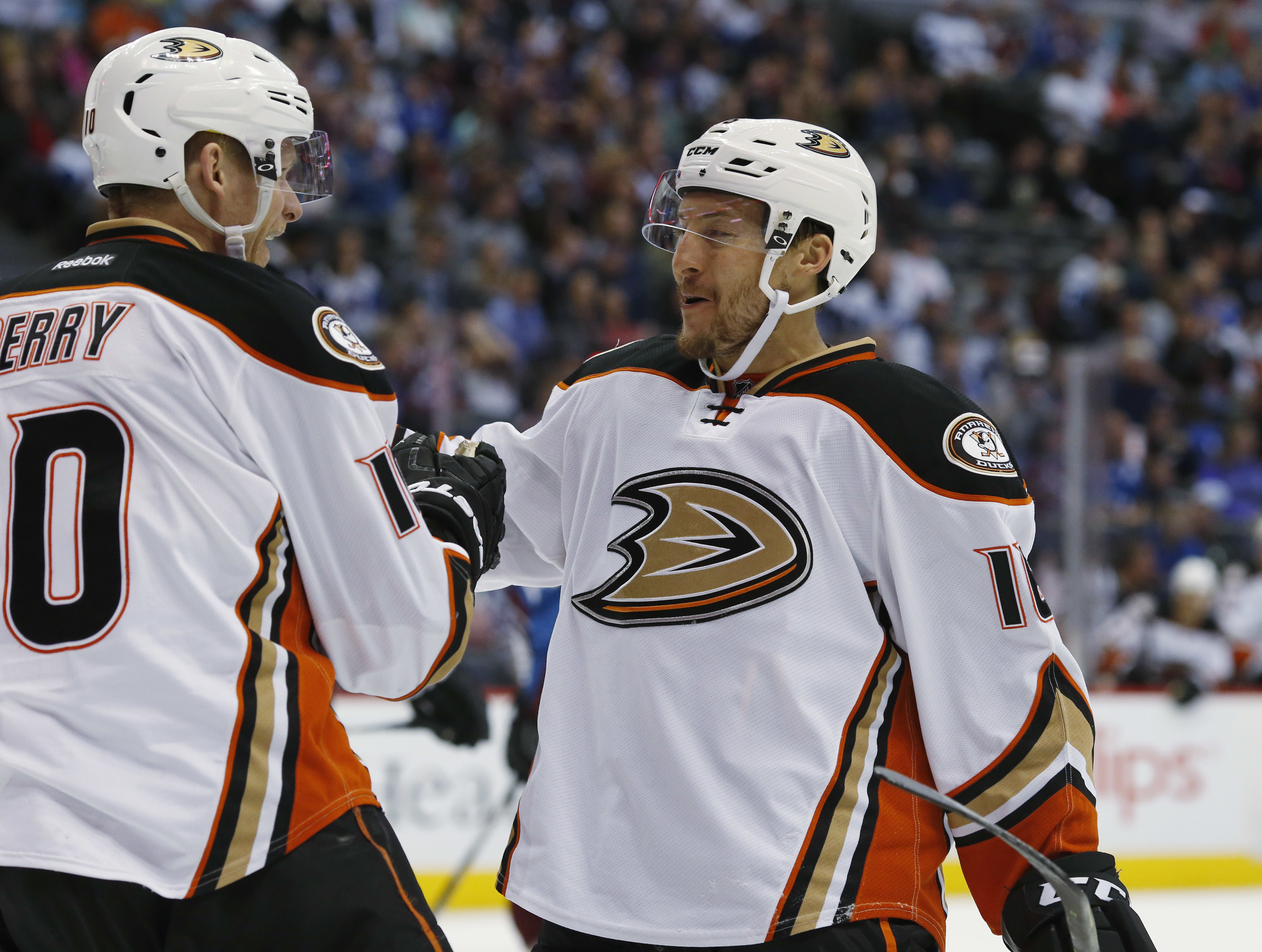 Anaheim Ducks right wing Corey Perry, left, congratulates left wing Ryan Garbutt after scoring a goal against the Colorado Avalanche in the second period of an NHL hockey game Saturday, April 9, 2016, in Denver. (AP Photo/David Zalubowski)