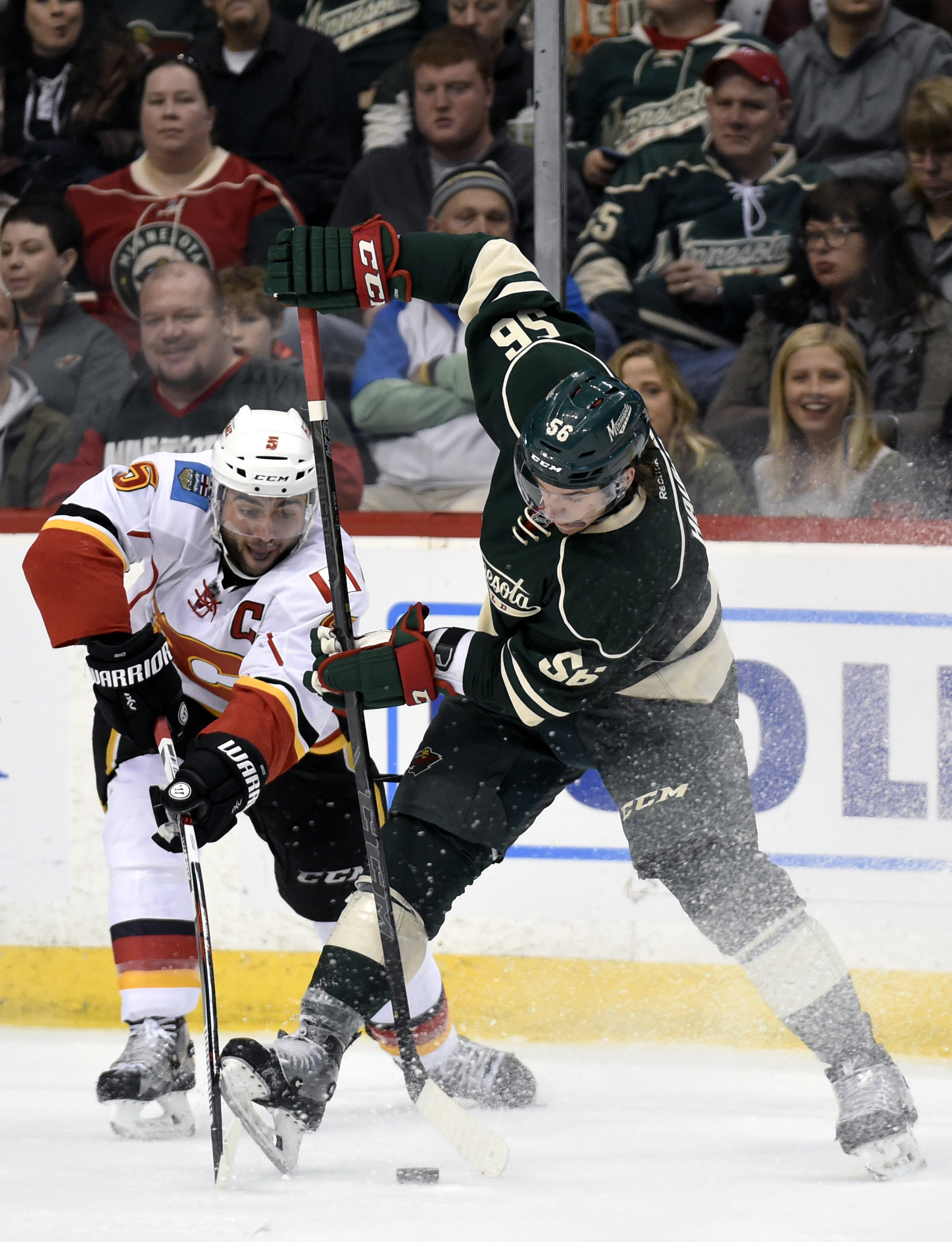 Calgary Flames' Mark Giordano, left, passes the puck away from Minnesota Wild's Erik Haula, of Finland, during the second period of an NHL hockey game Saturday, April 9, 2016, in St. Paul, Minn. (AP Photo/Hannah Foslien)