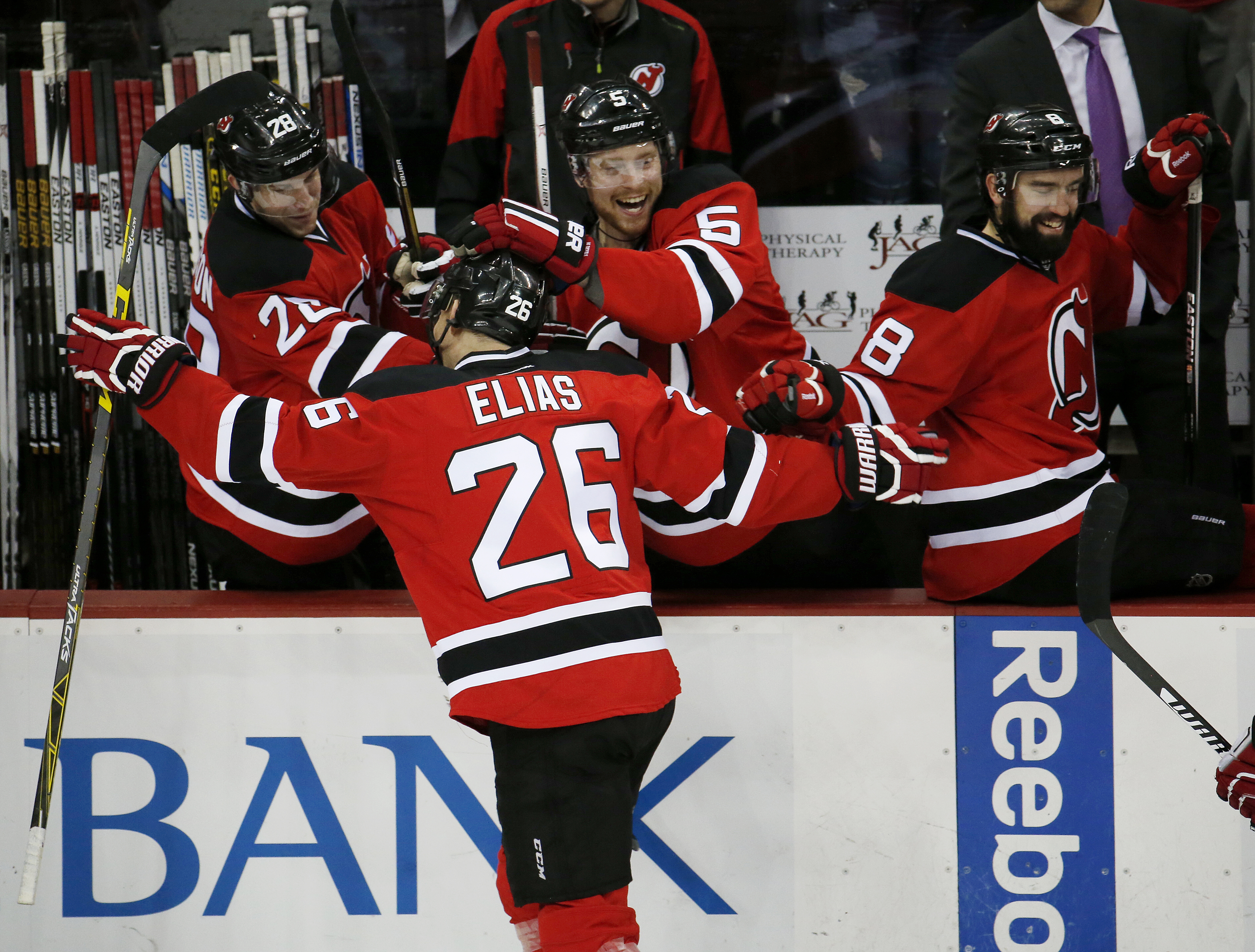 New Jersey Devils left wing Patrik Elias (26), of the Czech Republic, is mobbed by Damon Severson (28), Adam Larsson (5), of Sweden, and David Schlemko (8) after scoring a goal against the Toronto Maple Leafs during the third period of an NHL hockey game,