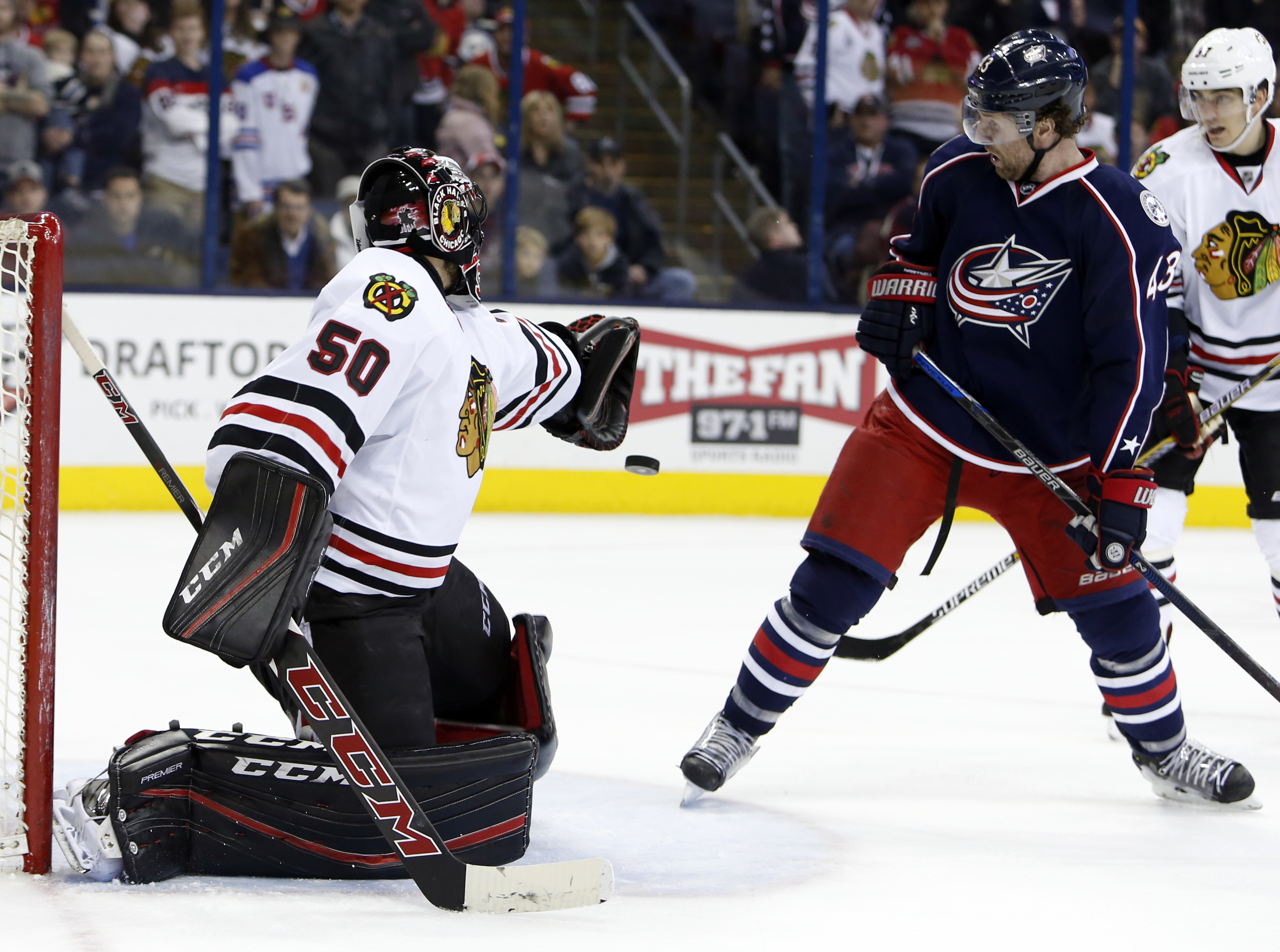 Columbus Blue Jackets' Scott Hartnell, right, deflects the puck into the goal against Chicago Blackhawks' Corey Crawford during the overtime period of an NHL hockey game Saturday, April 9, 2016, in Columbus, Ohio. The Blue Jackets beat the Blackhawks 5-4