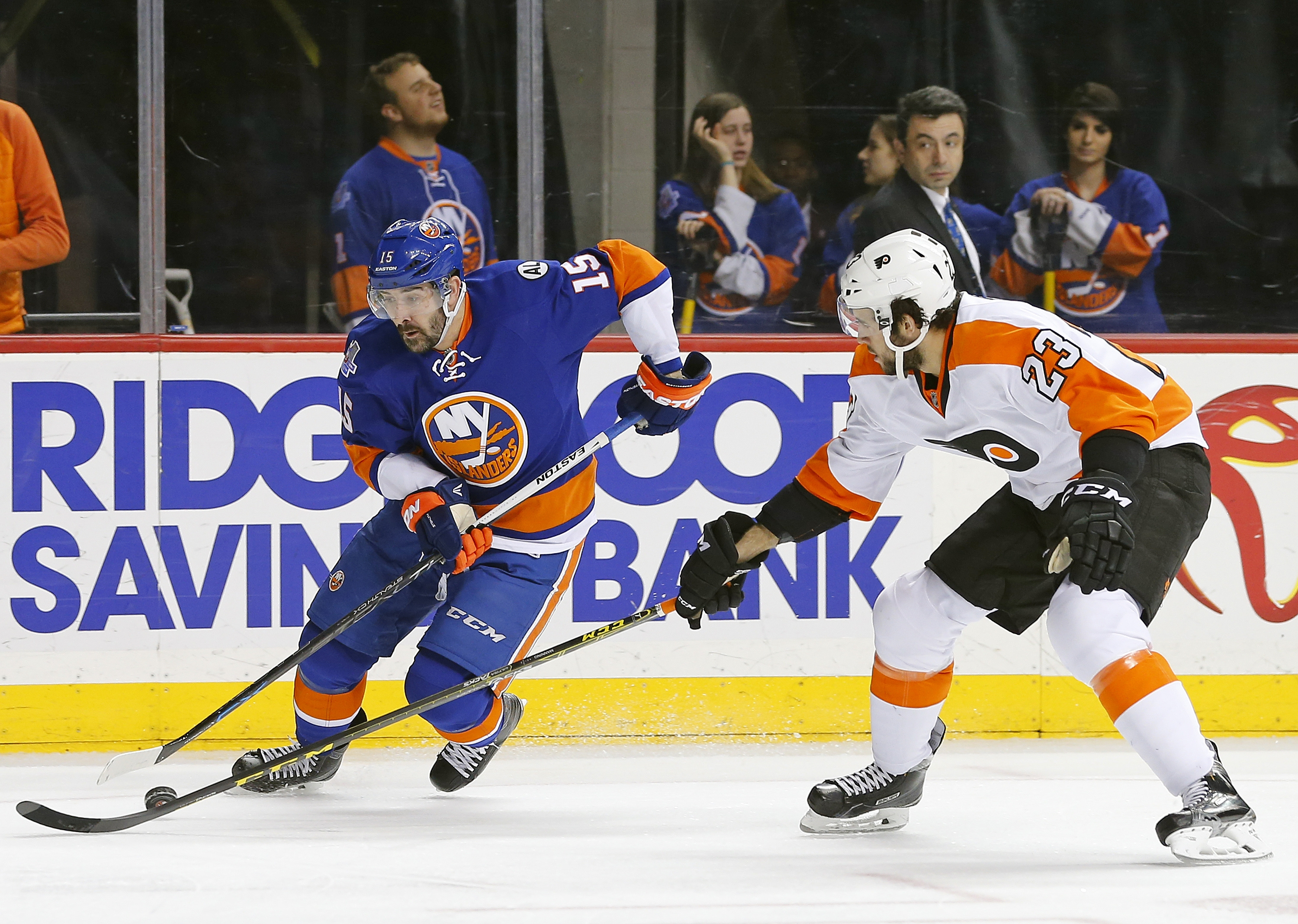New York Islanders  forward Cal Clutterbuck (15) moves the puck away from Philadelphia Flyers defensemen Brandon Manning (23) during the second period of an NHL hockey game in New York, Sunday, April 10, 2016. (AP Photo/Rich Schultz)