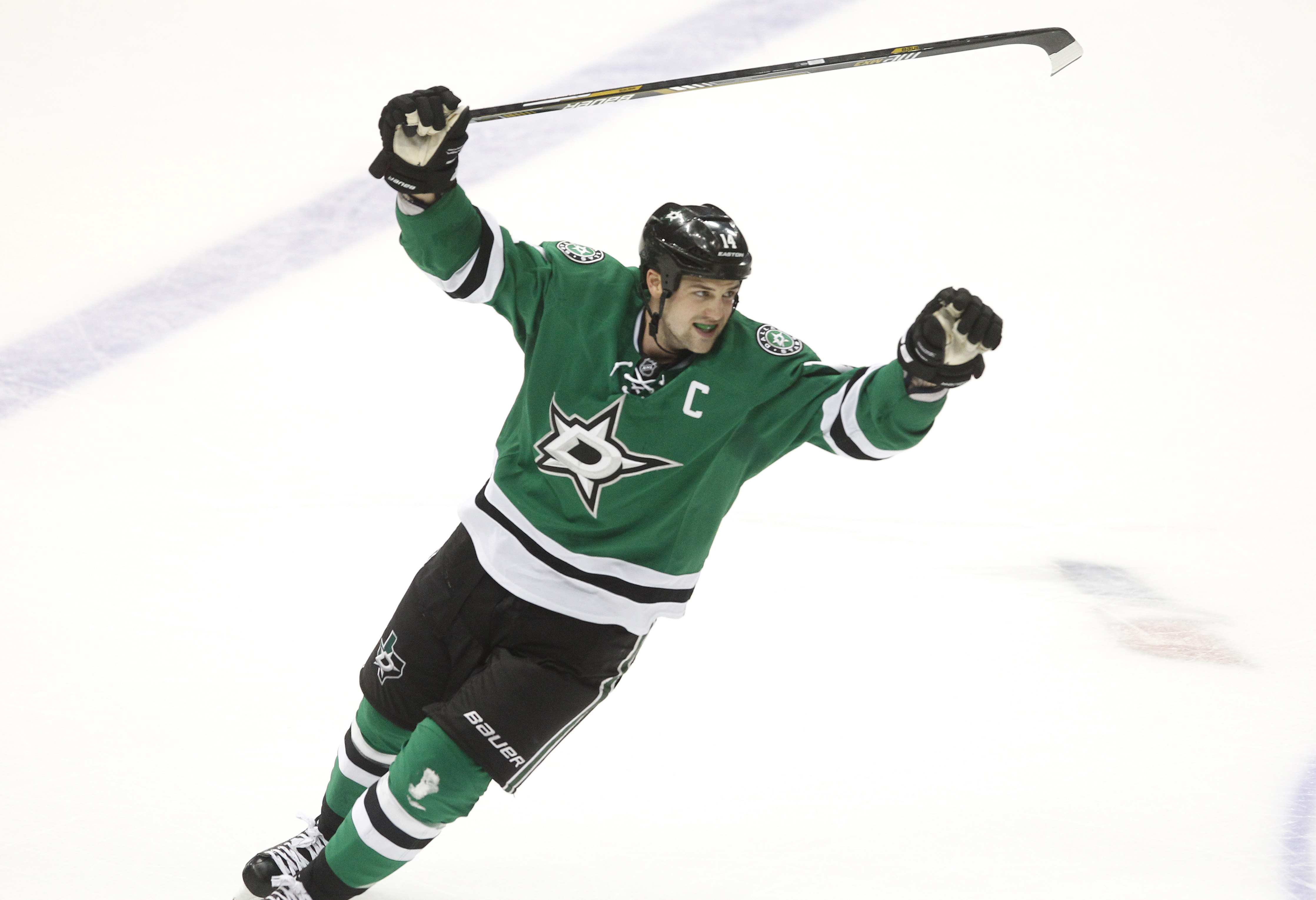 FILE - In this March 29, 2016, file photo, Dallas Stars left wing Jamie Benn celebrates teammate Patrick Sharp's goal against the Nashville Predators during the third period of an NHL hockey game in Dallas. Benn always seems uncomfortable in the spotlight