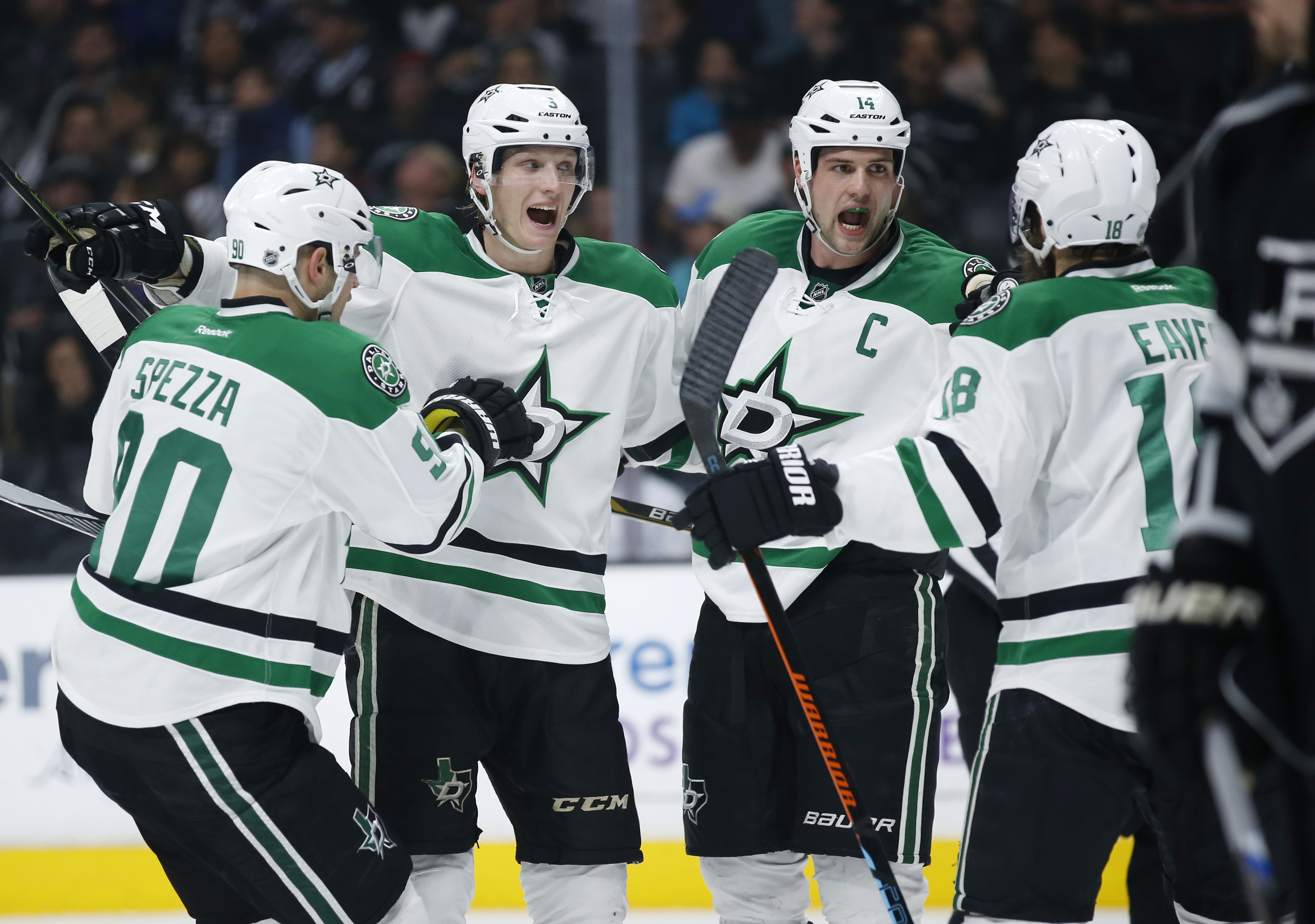 FILE - In this April 2, 2016, file photo, Dallas Stars left wing Jamie Benn, second from right, celebrates his power play goal with teammates, from left to right, Jason Spezza, John Klingberg and Patrick Eaves during the first period of an NHL hockey game