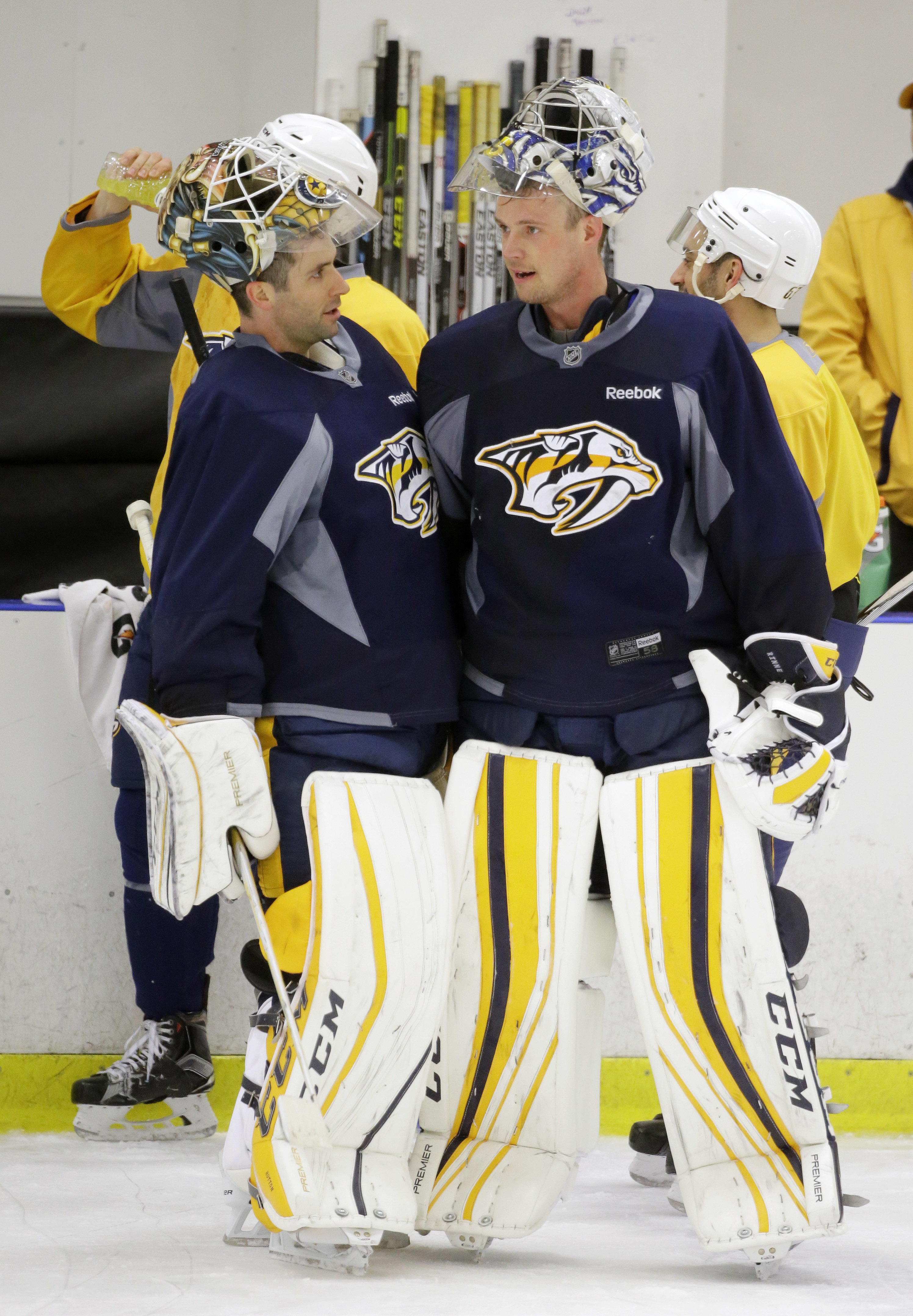 Nashville Predators goaltenders Carter Hutton, left, and Pekka Rinne, right, of Finland, talk during practice Tuesday, April 12, 2016, in Nashville, Tenn. The Predators are scheduled to play the Anaheim Ducks in the first round of the NHL Western Conferen