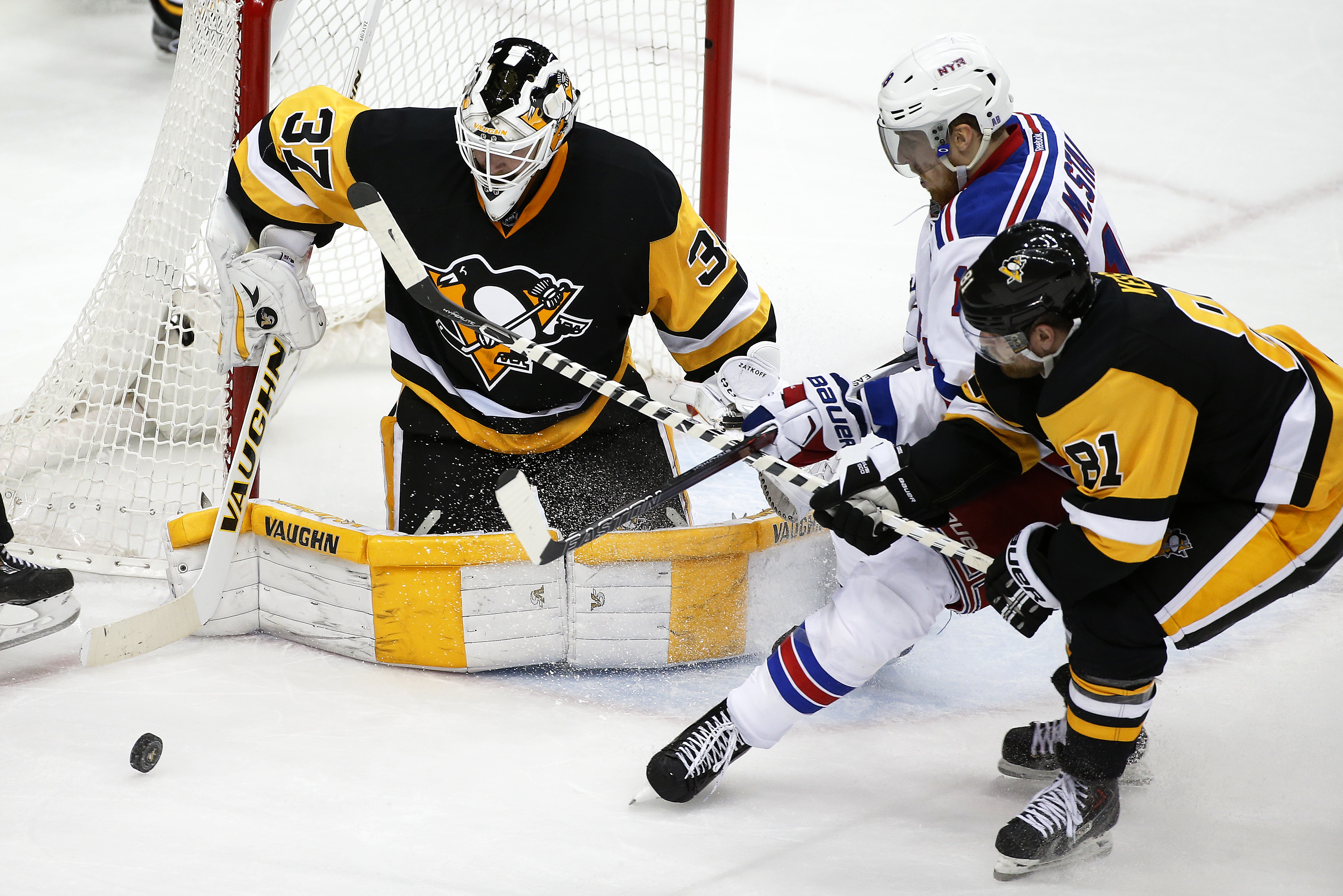 Pittsburgh Penguins goalie Jeff Zatkoff (37) stops a shot and Phil Kessel (81) lifts the stick of New York Rangers' Marc Staal to keep him from the rebound during the third period of a first-round NHL playoff hockey game in Pittsburgh, Wednesday, April 13
