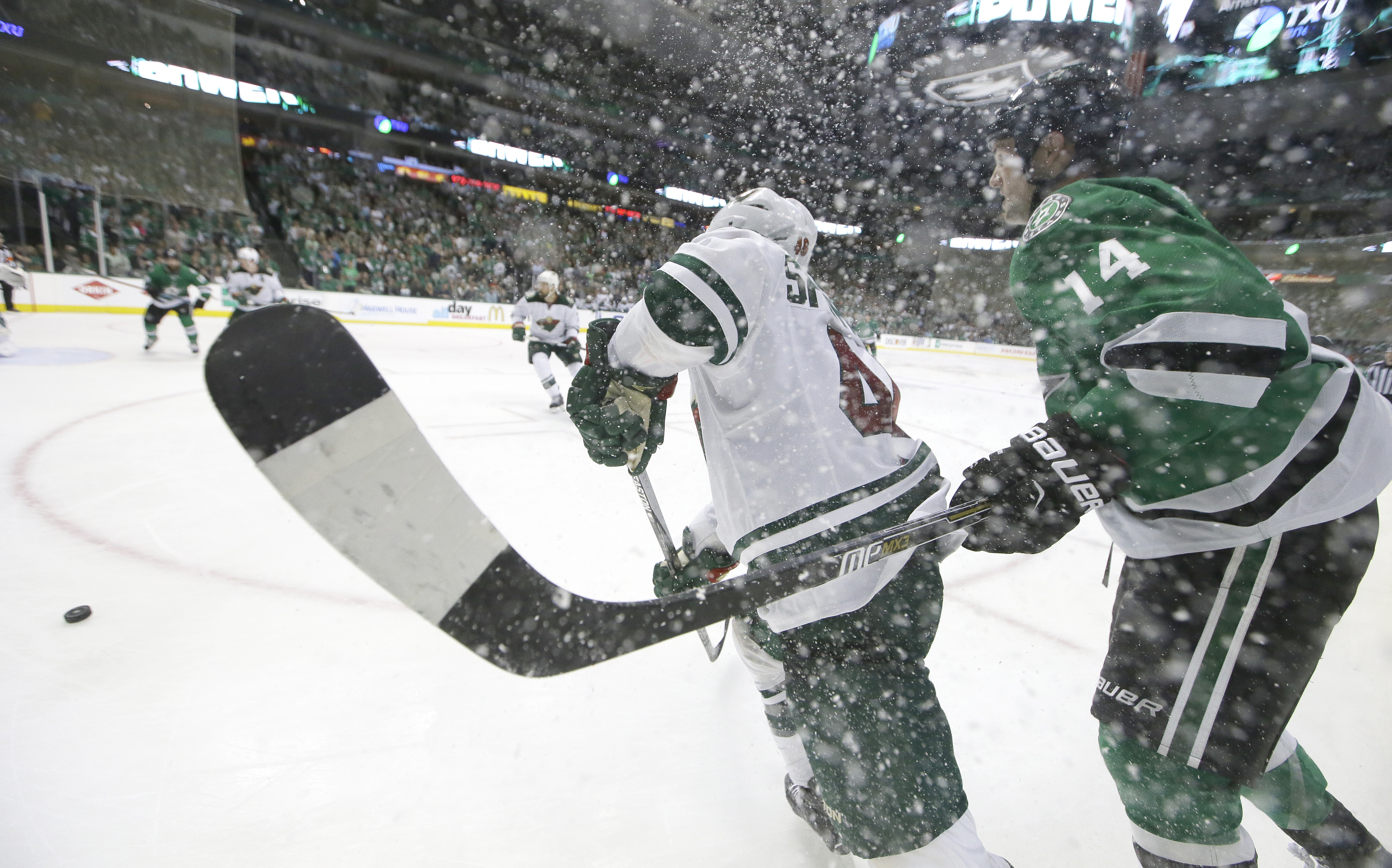 Dallas Stars left wing Jamie Benn (14) and Minnesota Wild defenseman Jared Spurgeon (46) chase the puck during the third period in Game 2 in the first round of the NHL Stanley Cup playoffs Saturday, April 16, 2016, in Dallas. (AP Photo/LM Otero)