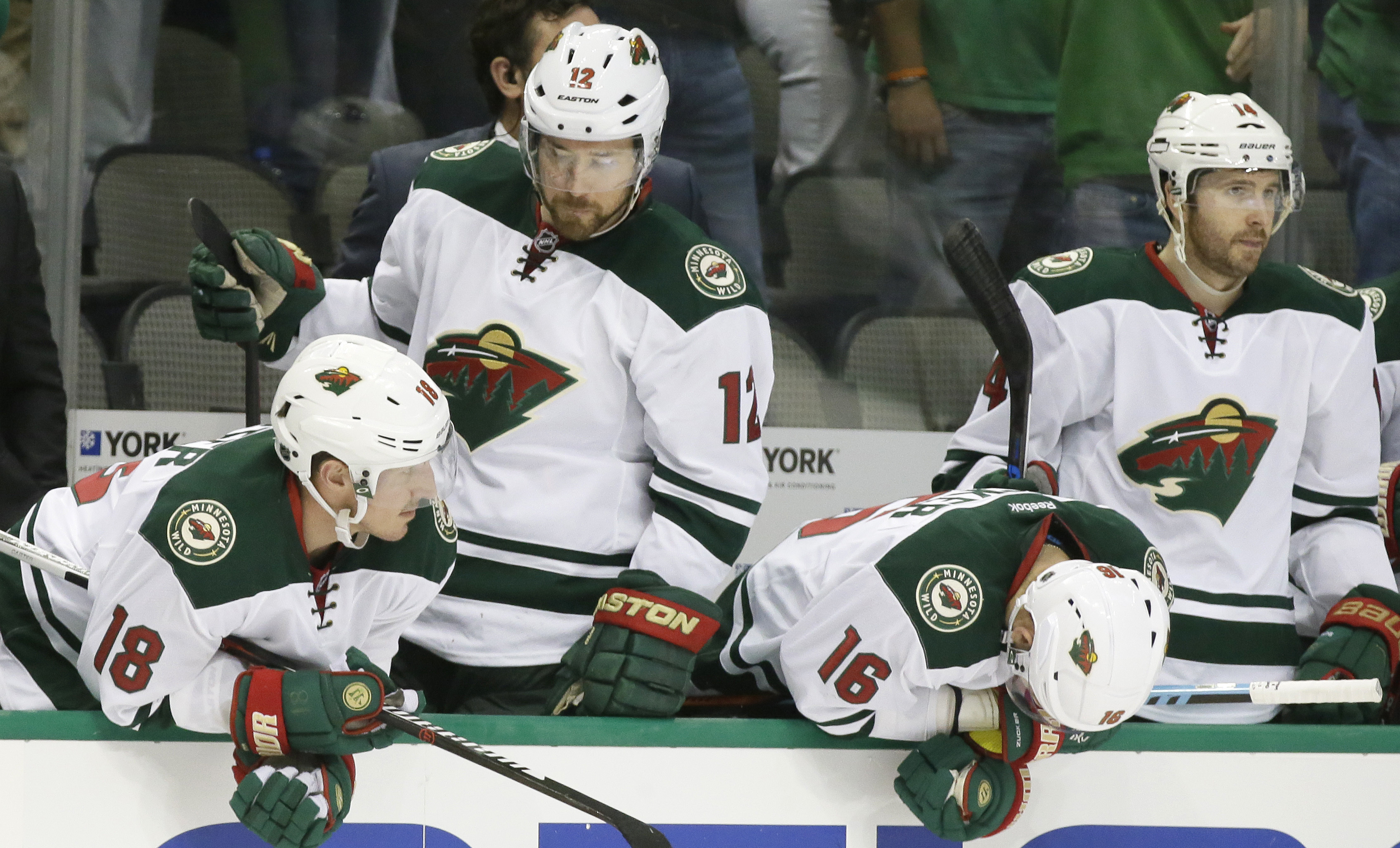 Minnesota Wild Ryan Carter (18), David Jones (12), Jason Zucker (16) and Justin Fontaine (14) react on the bench after  the the third period in Game 2 in the first round of the NHL Stanley Cup playoffs against the Dallas Stars, Saturday, April 16, 2016, i